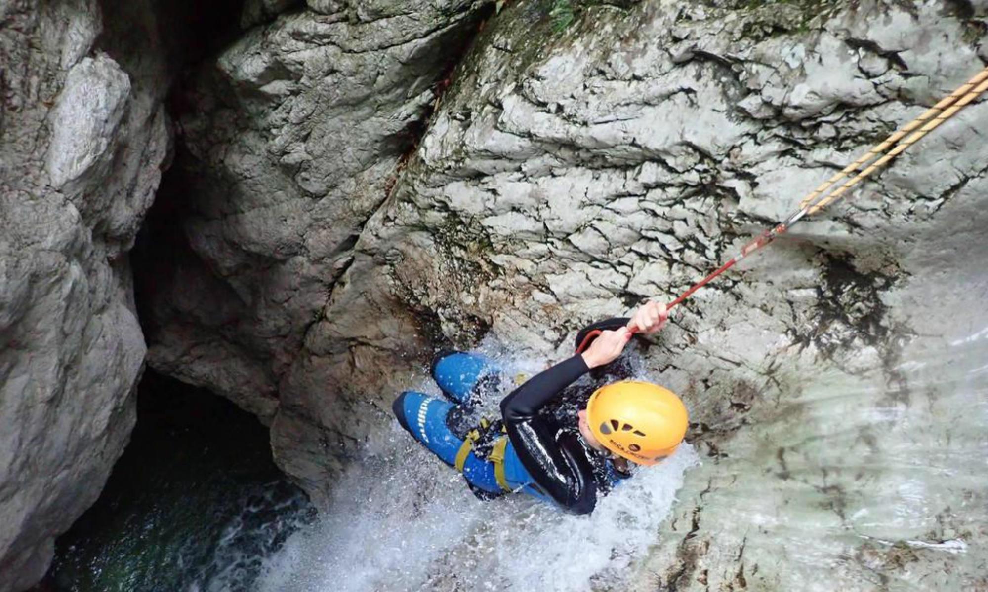Una persona si sta calando in una pozza d'acqua durante il canyoning in Slovenia.