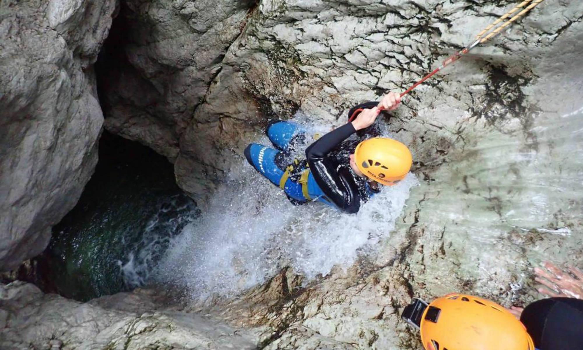 Am Wildfluss Sušec im Soča Tal seilt sich eine Canyoning Tour Teilnehmerin an einem Wasserfall ab.
