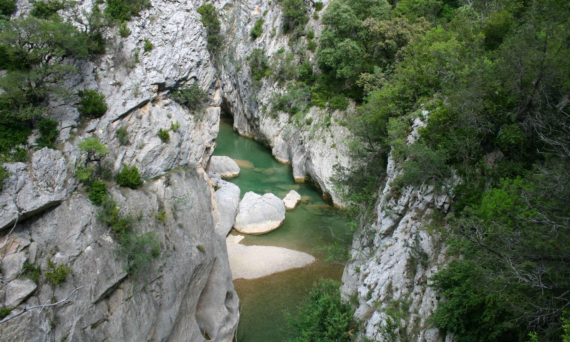 Il canyon Sierra de Guara si dirama mostrando massi chiari e acqua verde.