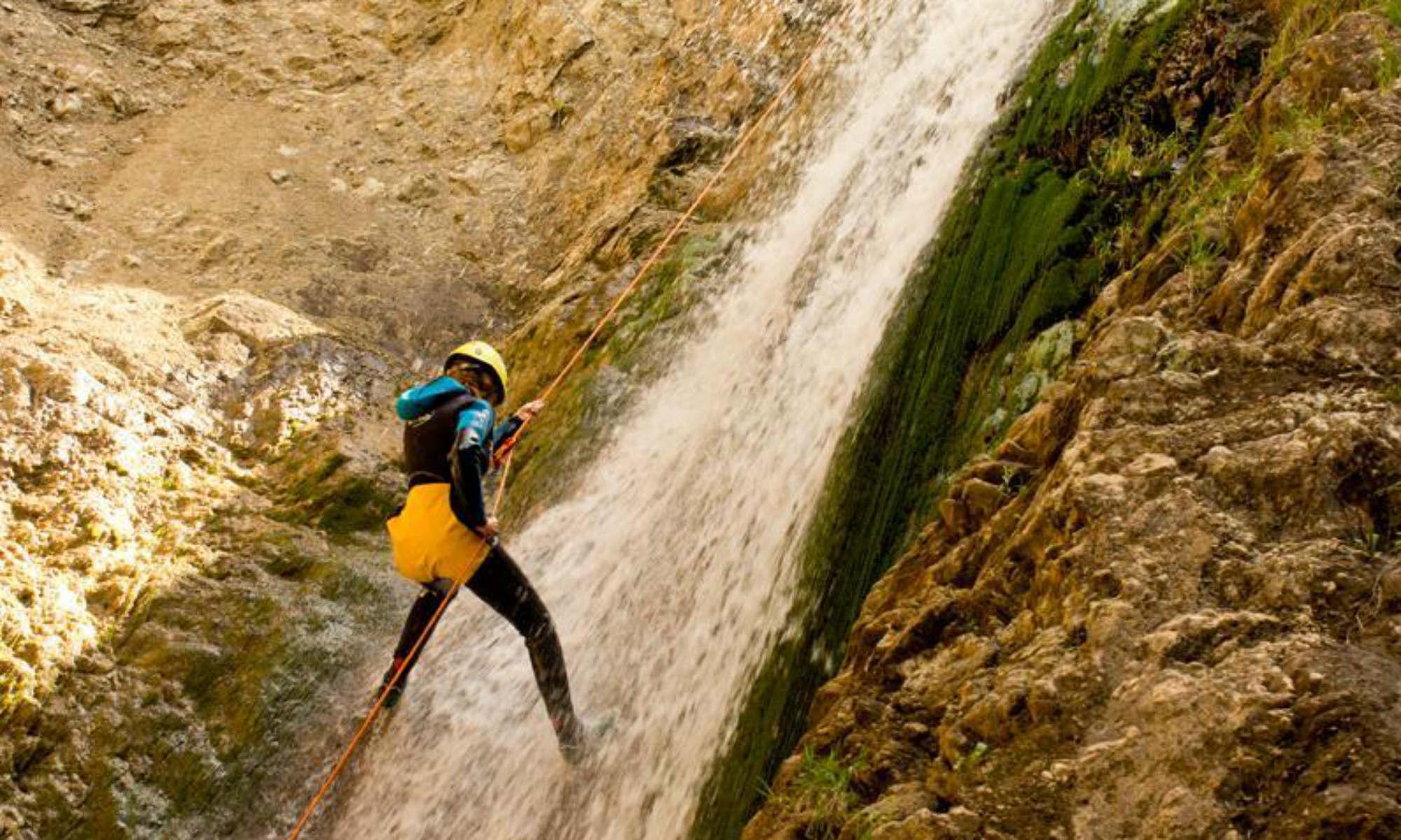 Ein Teilnehmer seilt sich beim Canyoning in Spanien an einem Wasserfall ab.