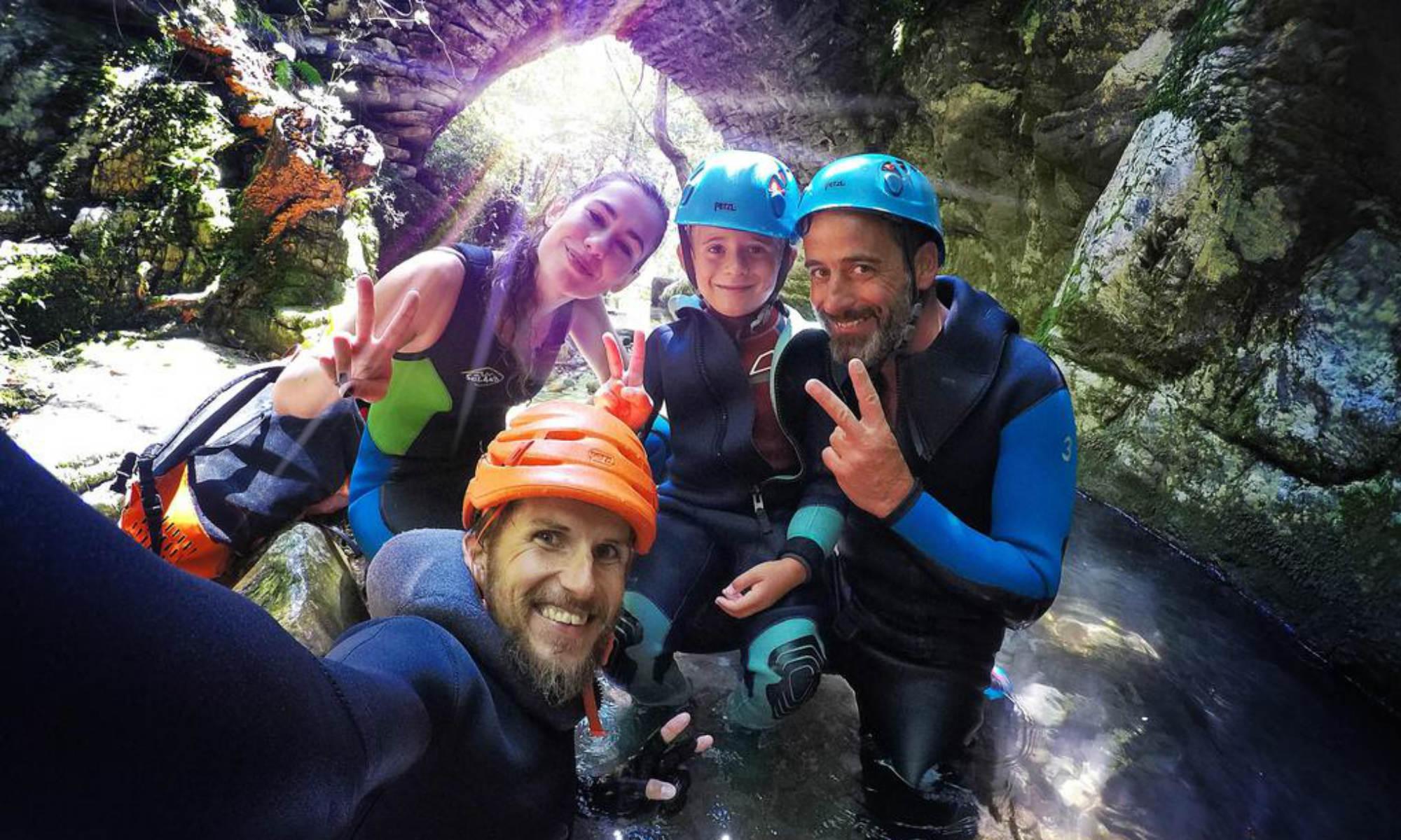 Una famiglia è in posa e sta per cominciare a fare canyoning in Italia.