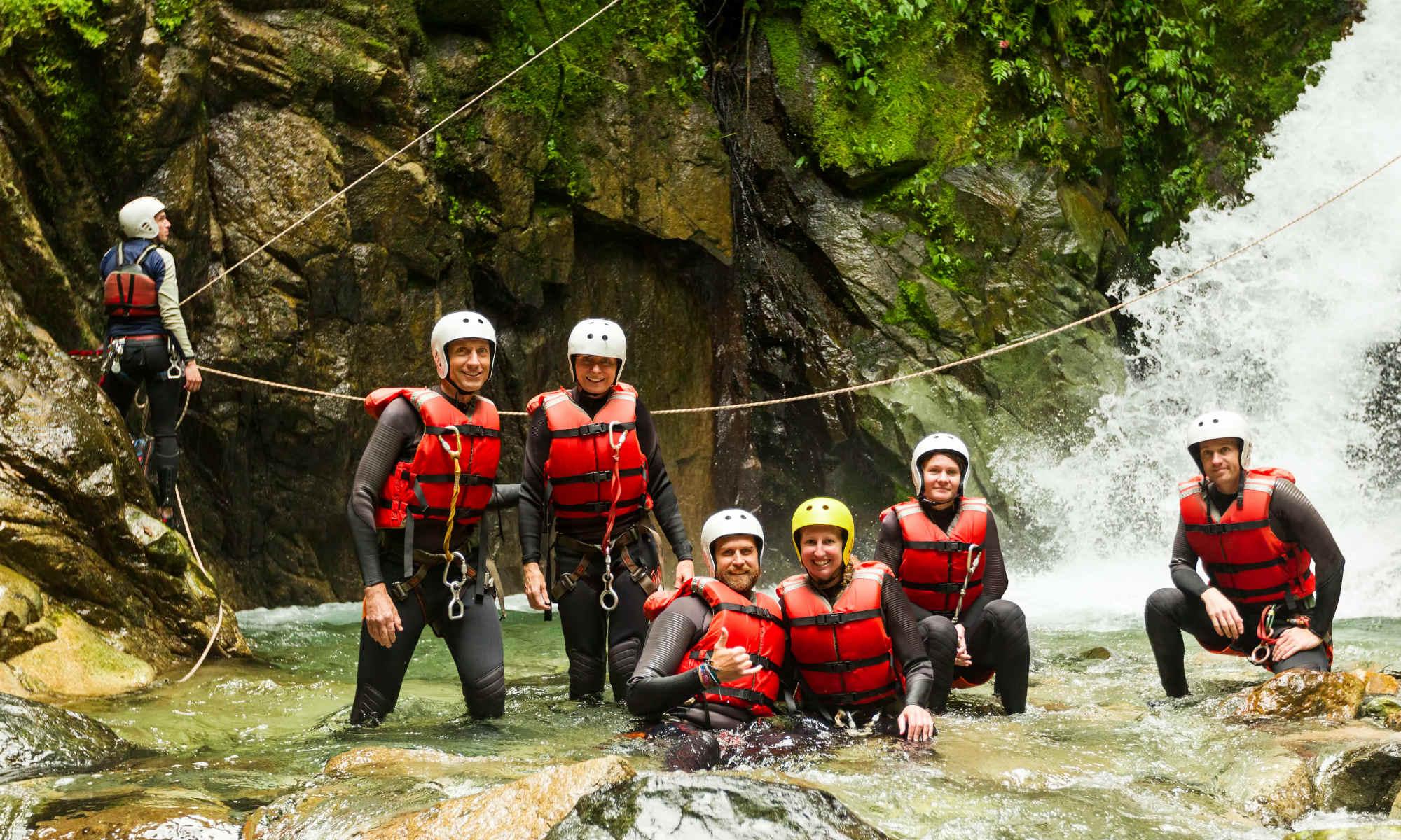 Eine Gruppe während einer Canyoning Tour vor einem Wasserfall.