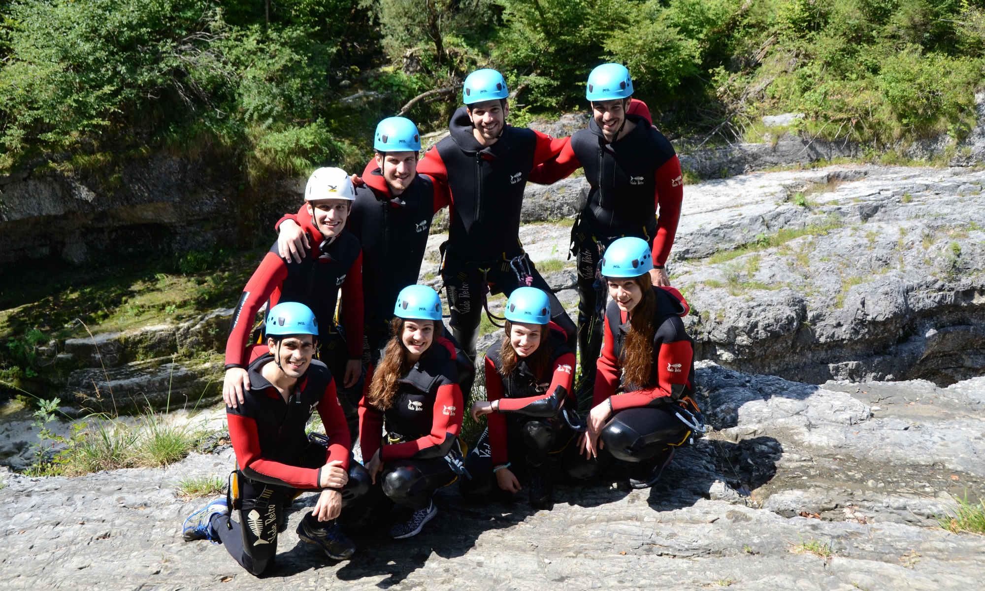 Un gruppo ha indossato l'attrezzatura, tuta, imbragatura e casco ed è pronto per fare canyoning.
