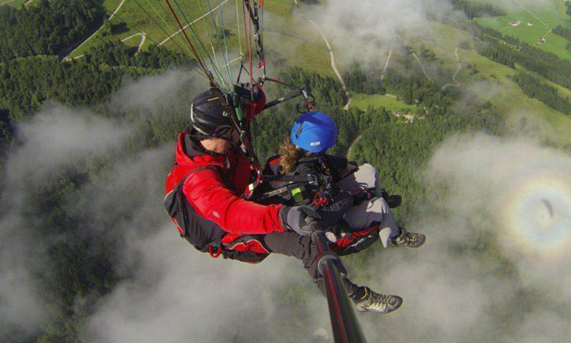 Ein Paragliding Pilot und sein Passagier während eines Fluges über den Chiemgau.