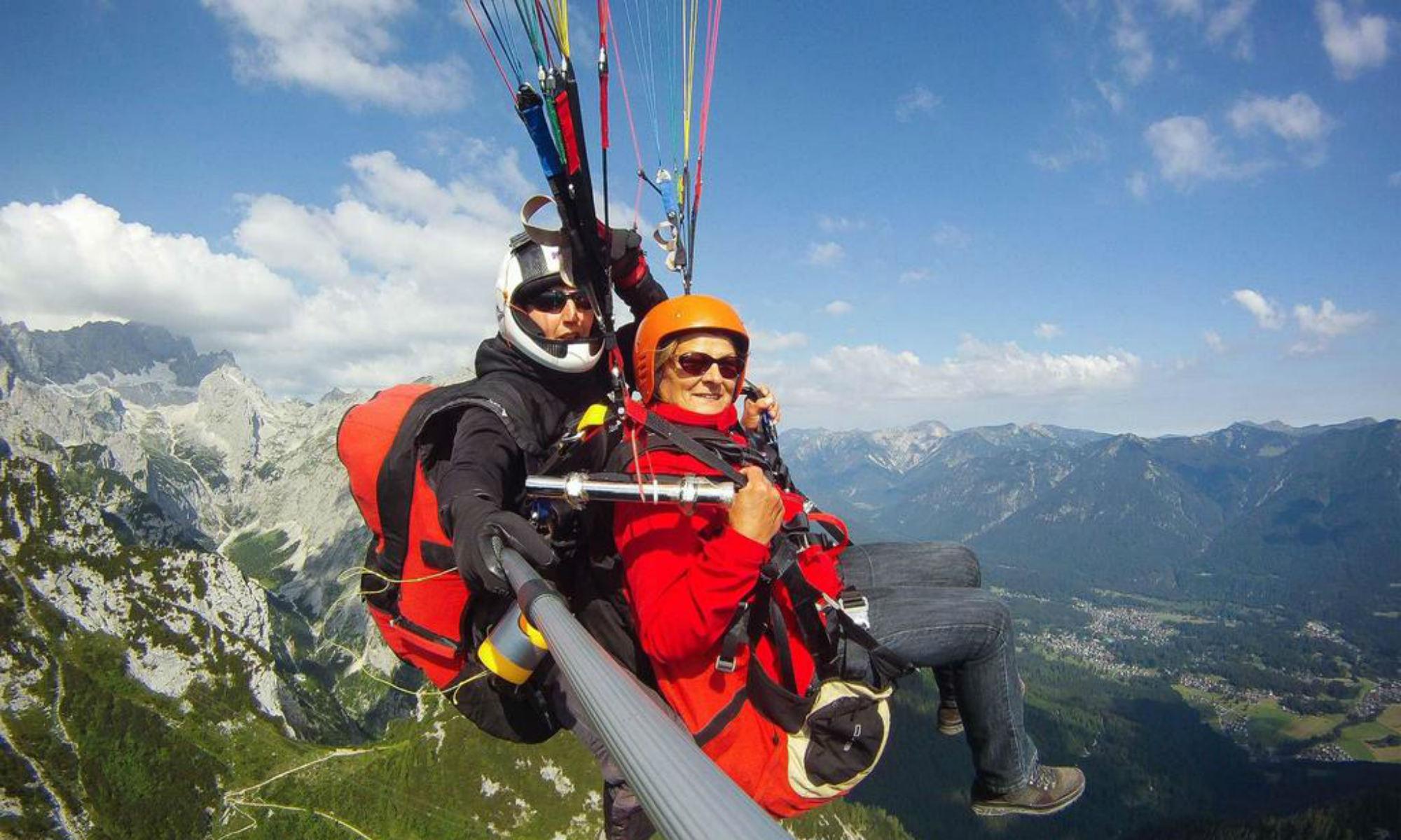 Eine Frau und ein Mann während eines Paragliding Flugs in Garmisch-Partenkirchen.