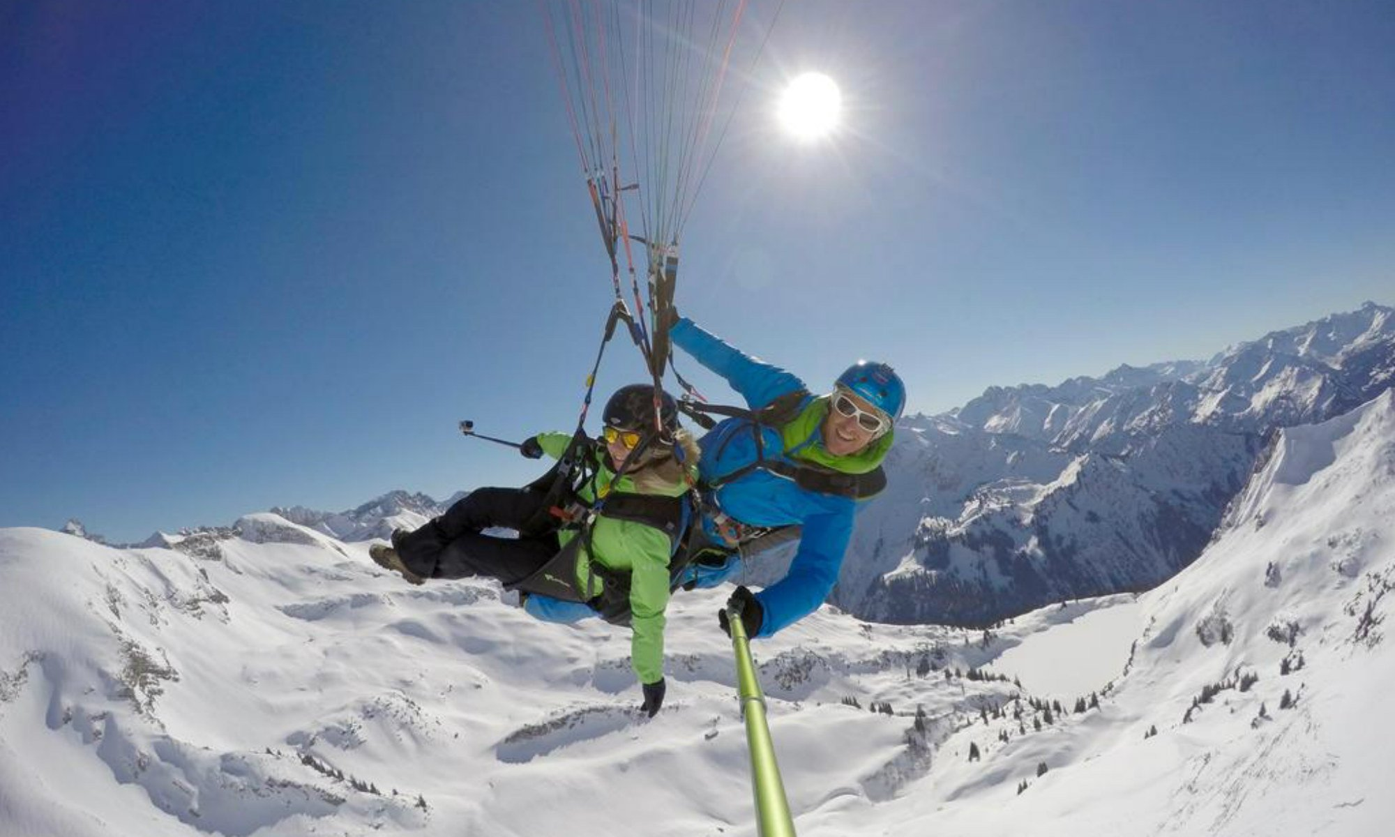 Ein Paraglider und sein Passagier bei einem Flug über Oberstdorf im Winter.