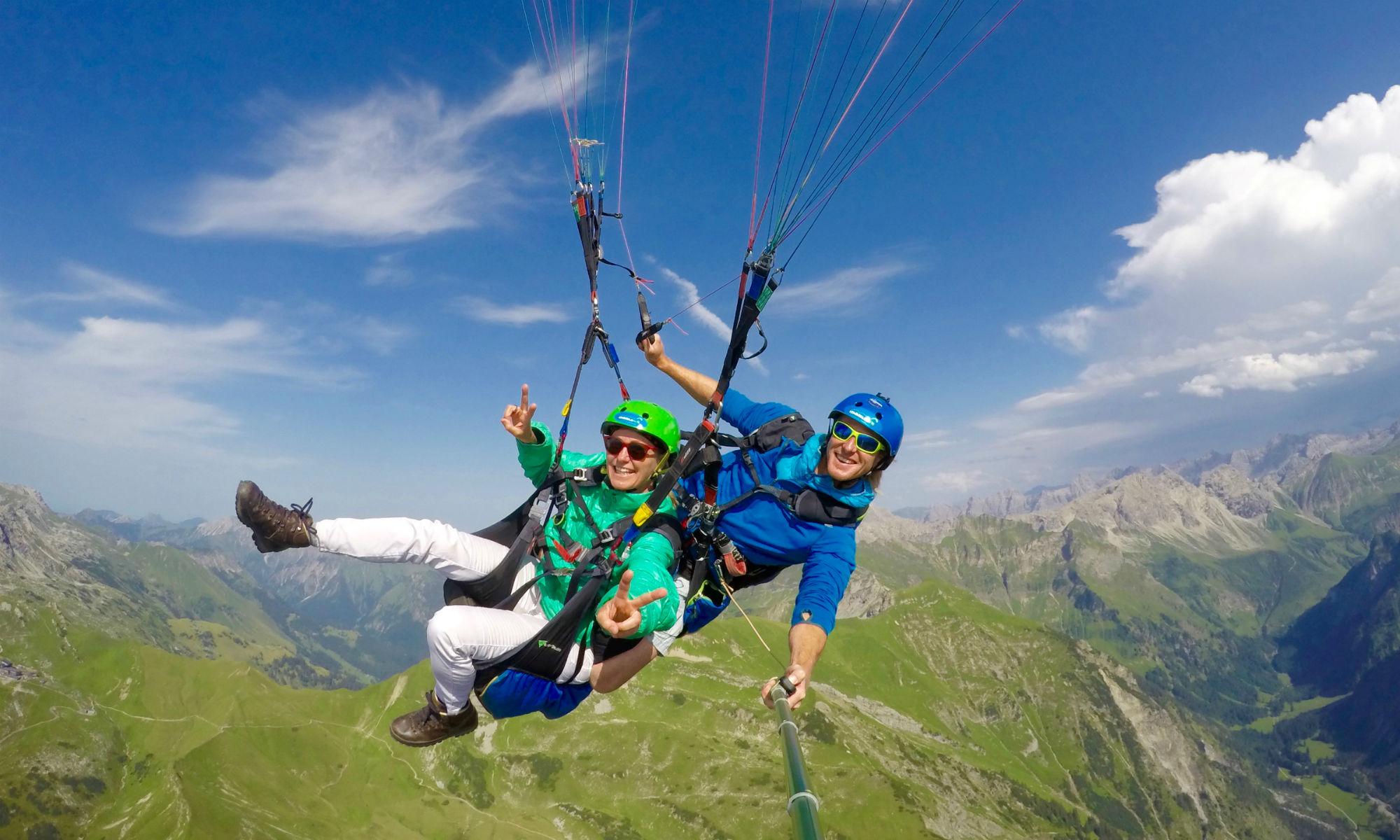 Ein Tandem-Pilot mit Passagier während eines Akrobatikfluges im bayerischen Allgäu.