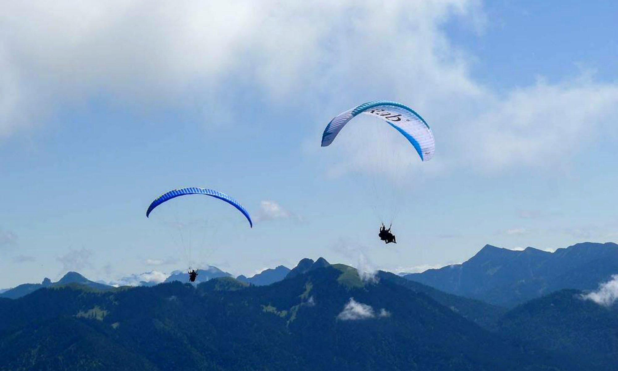 Das Bergpanorama der Bayerischen Alpen mit 2 Paraglidern im Vordergrund.