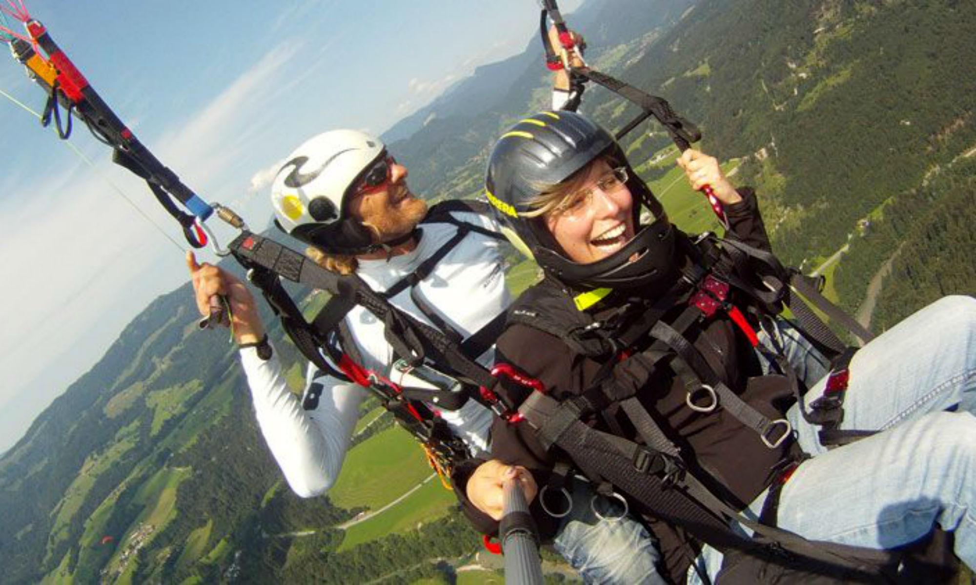 Ein Paragliding Pilot mit Passagier während eines Fluges.