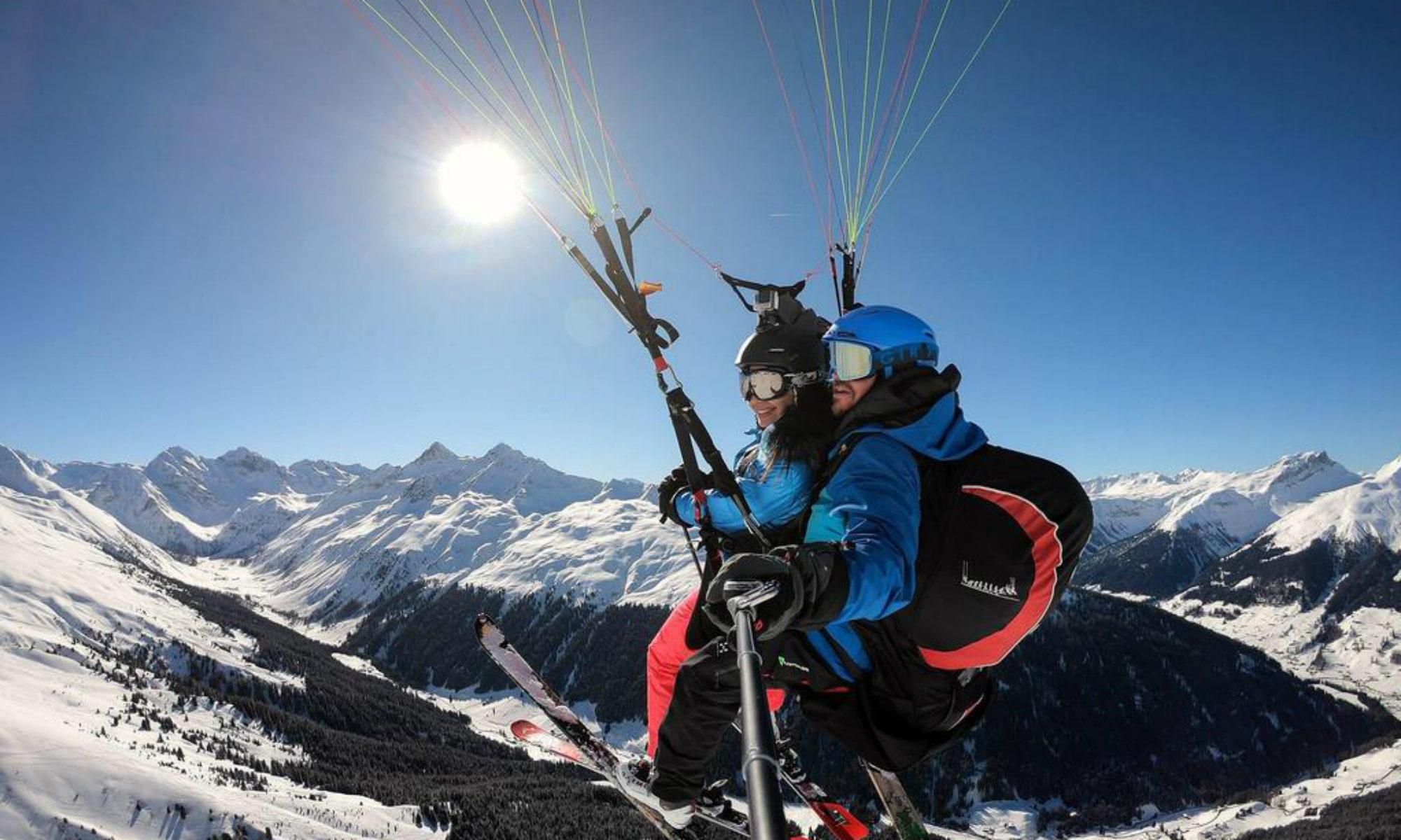 Ein Paragliding Pilot mit Passagier über den Bergen der Region Davos-Klosters.