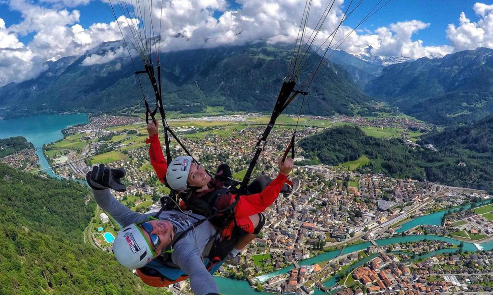 Ein Tandem Pilot mit seinem Passagier über der Stadt Interlaken.
