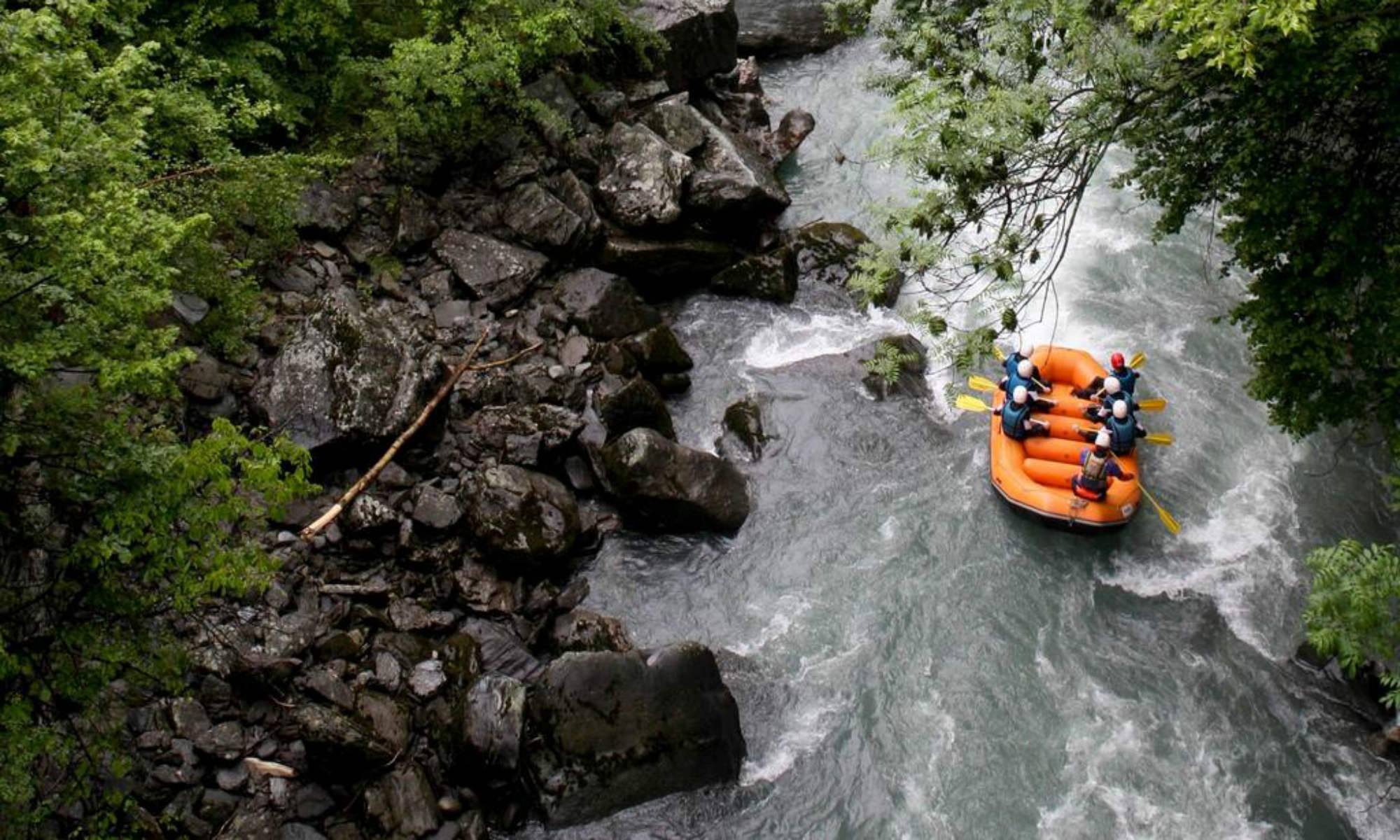 Un raft supera un passaggio stretto del fiume sulla Dora Baltea.