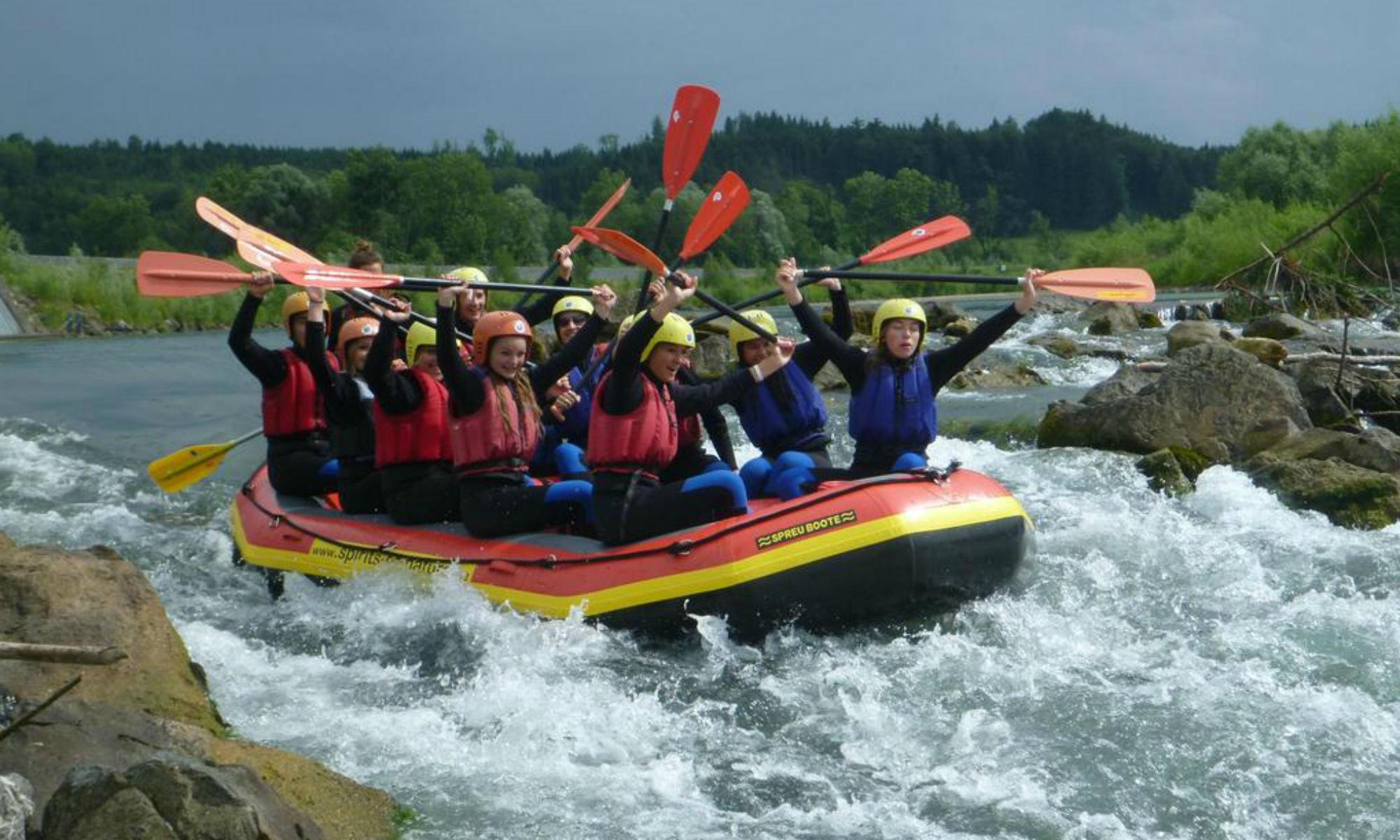 Eine Gruppe in einem großen Schlauchboot beim Rafting im Allgäu.