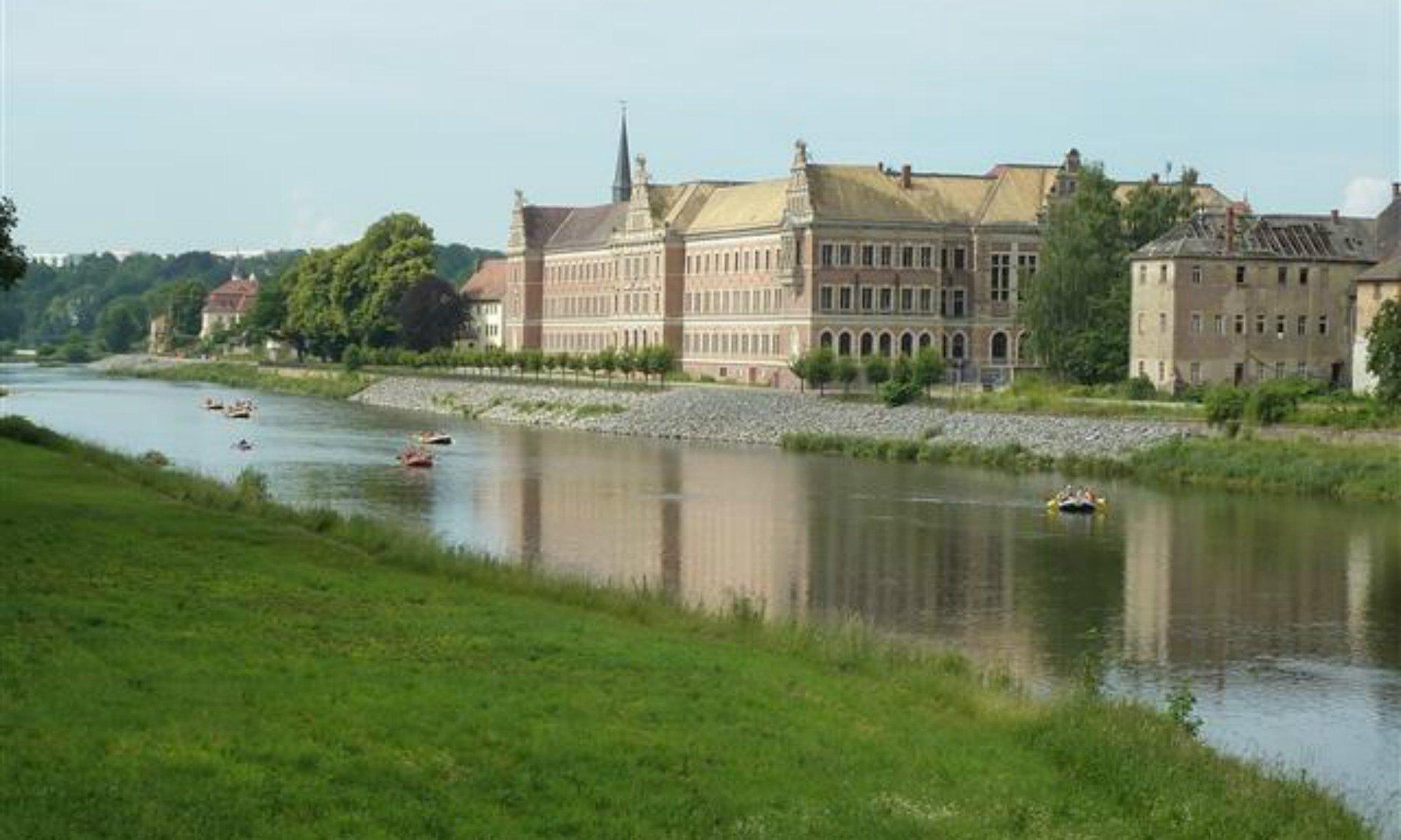 Einige Rafting Boote fahren auf der Mulde, im Hintergrund sieht man das Gymnasium St. Augustin.
