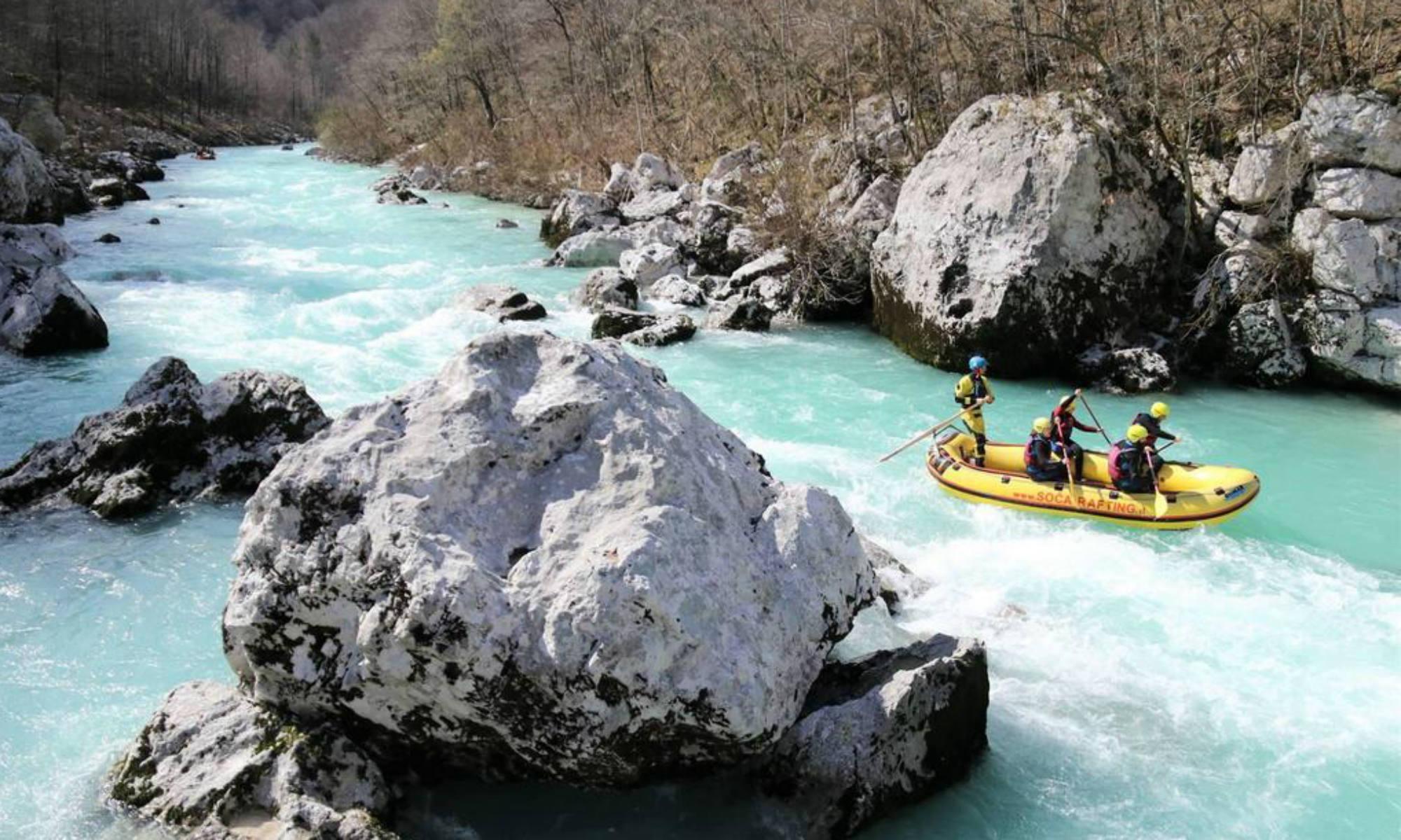 Eine Gruppe von Personen fährt bei ihrer Rafting Tour durch felsige Hindernisse auf der Soča.
