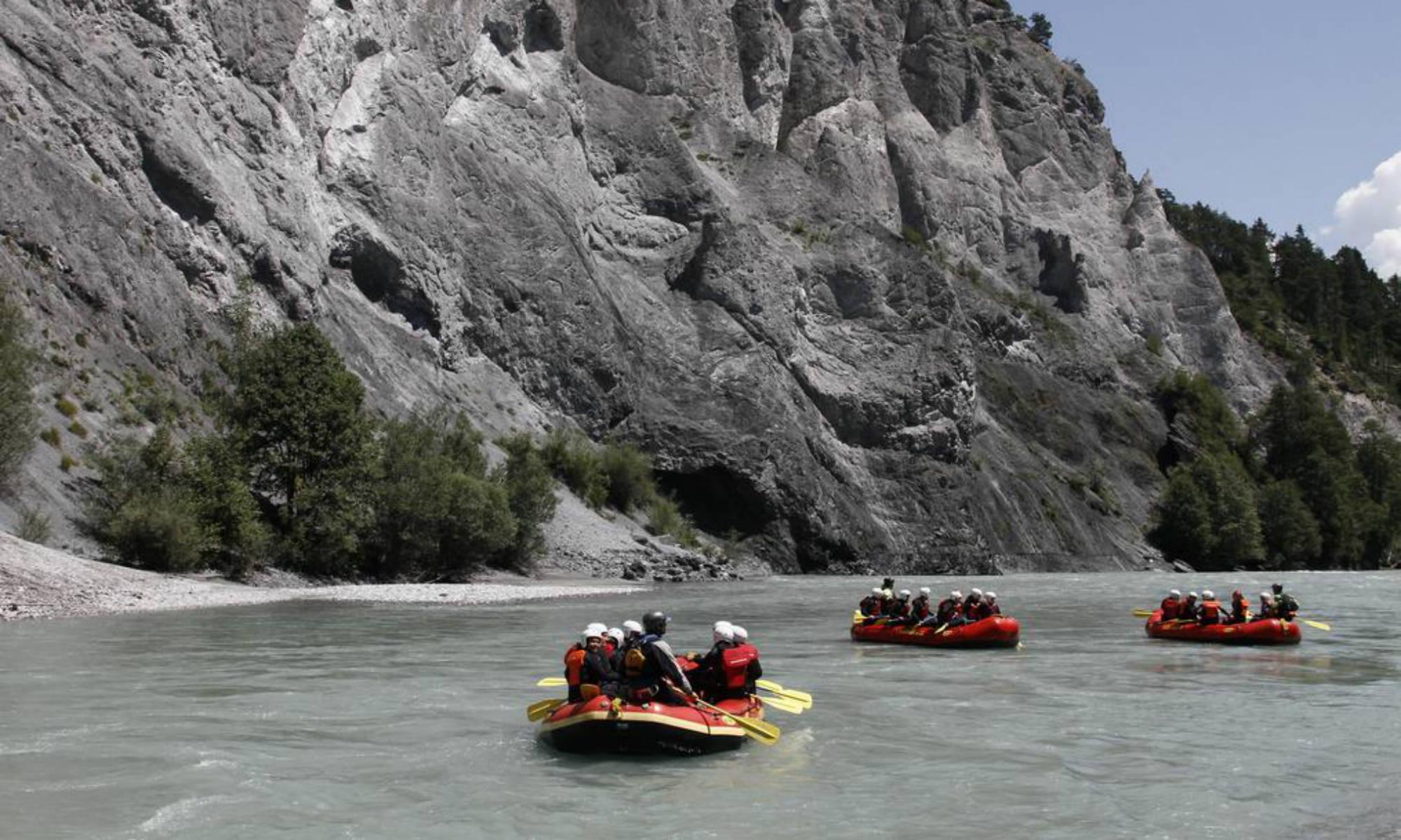 Un gruppo di raft passa vicino ad alte pareti rocciose.