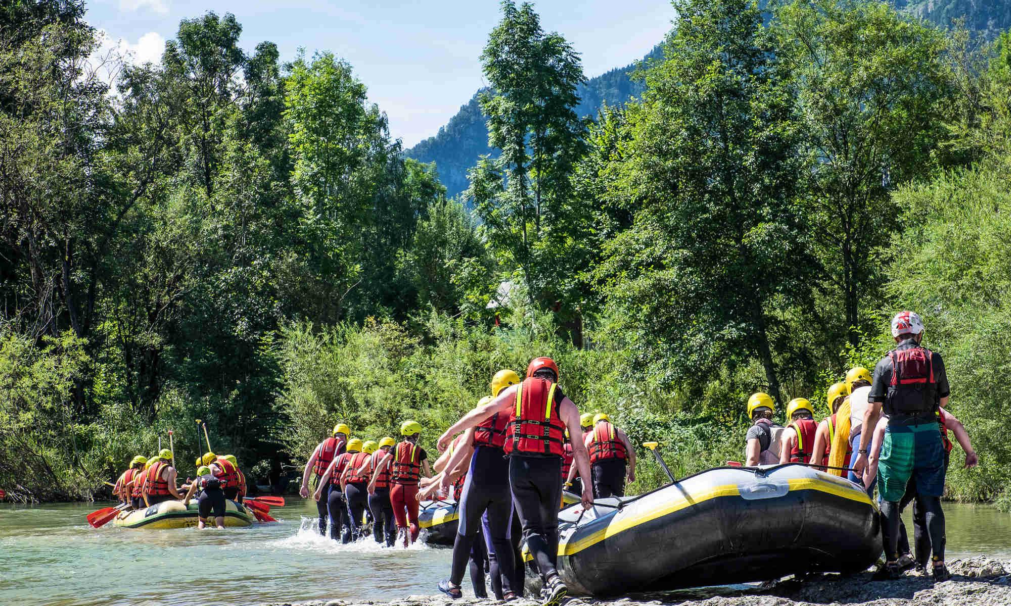 Mehrere Gruppen tragen Schlauchboote zur Einstiegsstelle am Fluss.