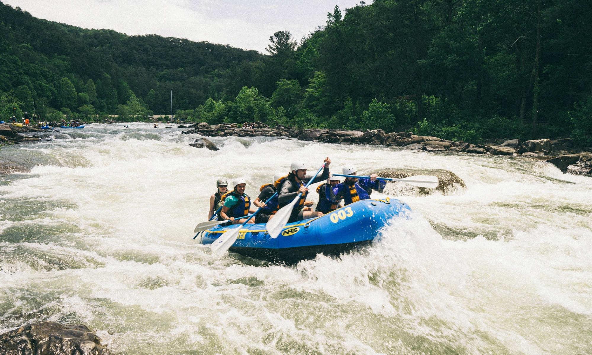 Eine Gruppe beim Wildwasser Rafting auf einem bewegten Fluss.