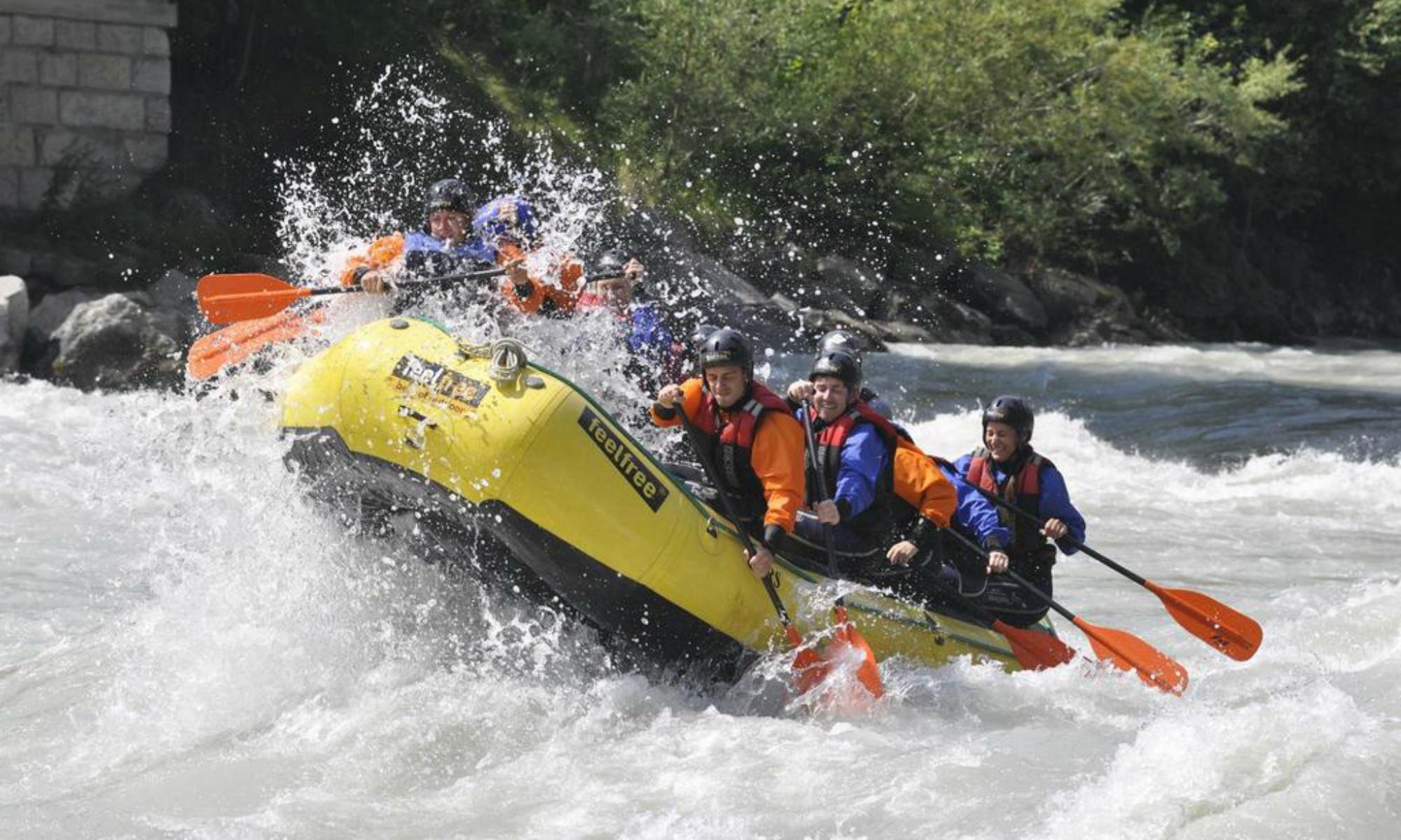 Eine Gruppe von Personen beim Rafting in einem Schlauchboot auf der Ötztaler Ache.