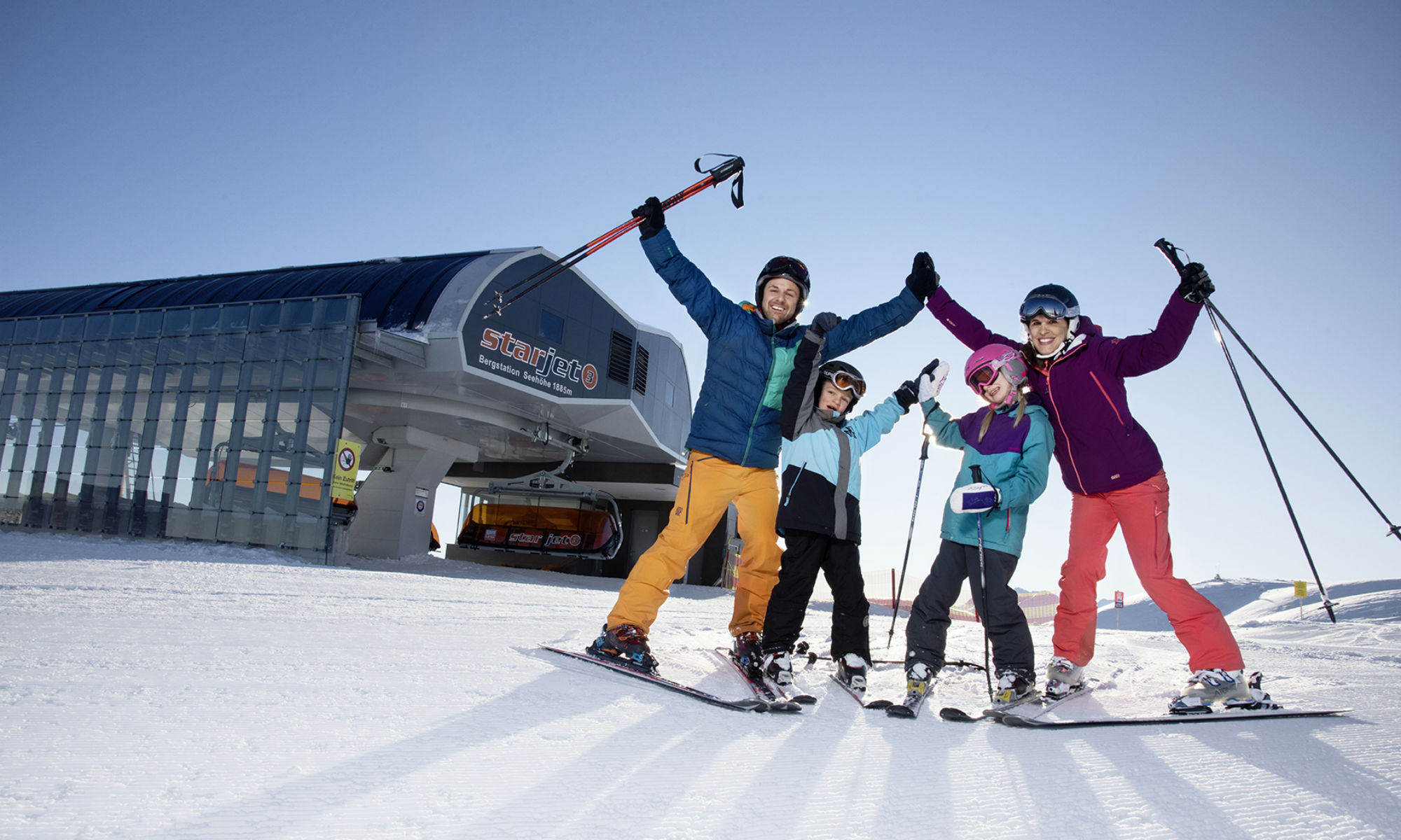 Eine Familie wirft vor der Bergstation in Flachau die Hände voller Freude in die Luft.