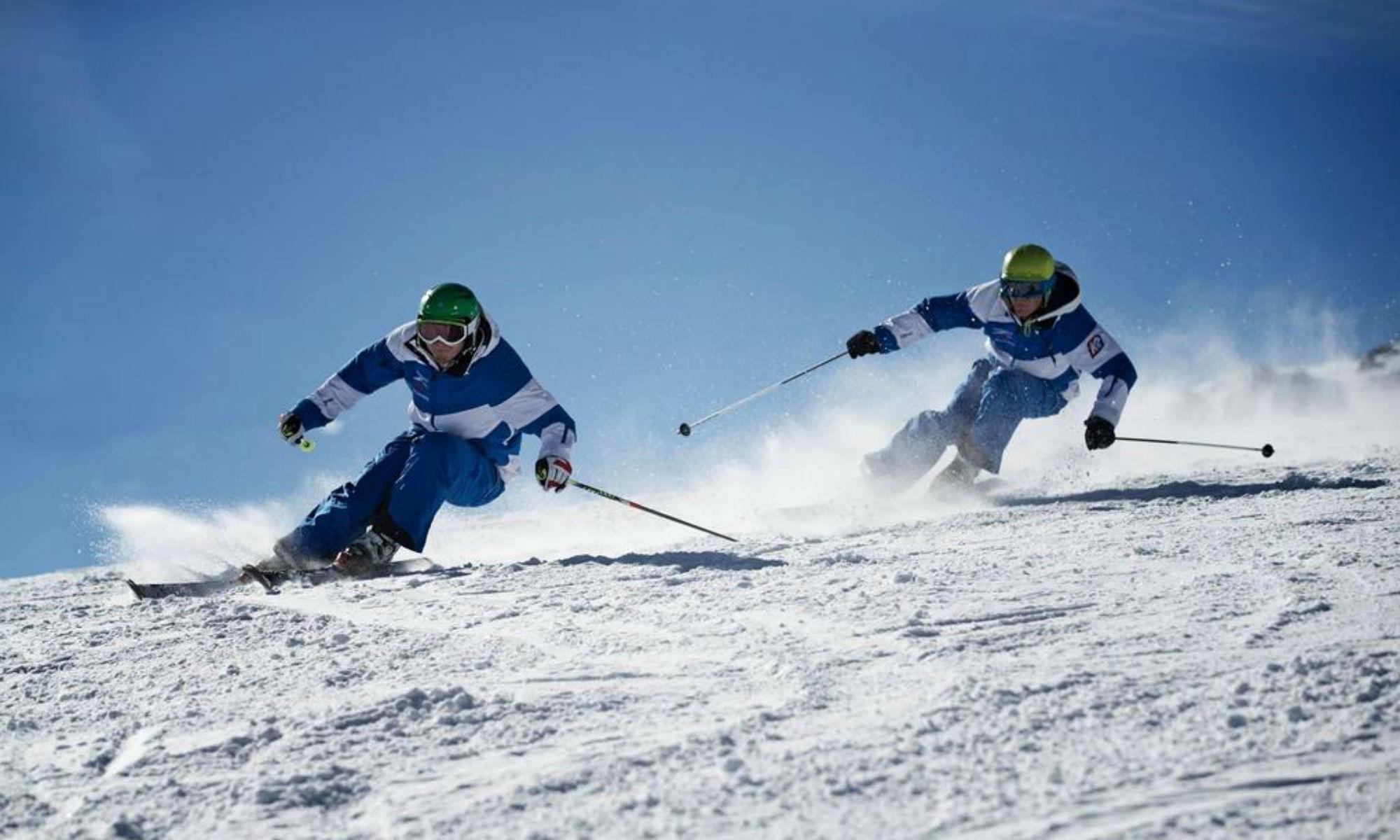 Zwei Skifahrer ziehen bei Sonnenschein ihre Schwünge im Schnee bei Garmisch-Partenkirchen.