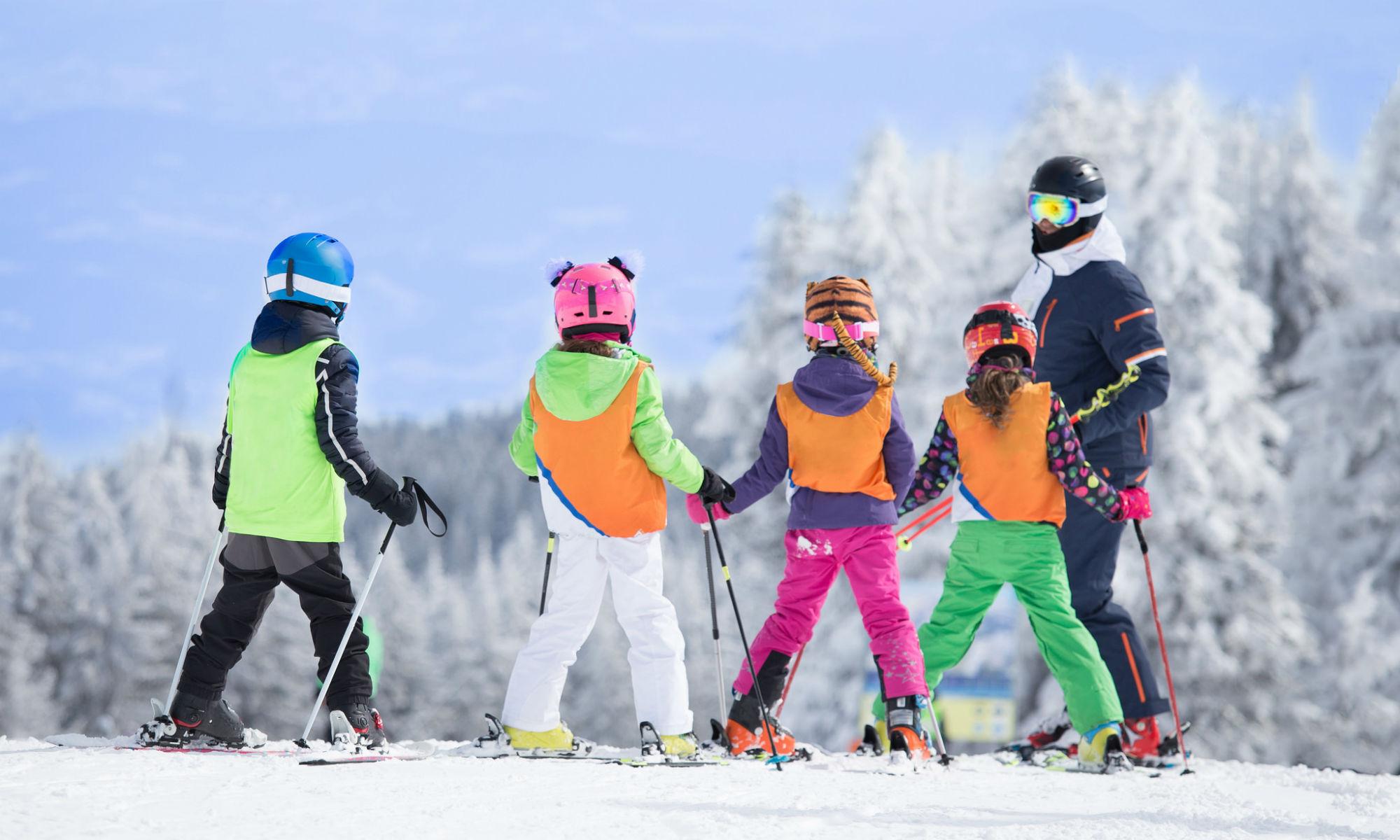 Ein Skilehrer gibt einer Gruppe von Kindern Skiunterricht auf einer Piste im Skigebiet Arosa Lenzerheide.