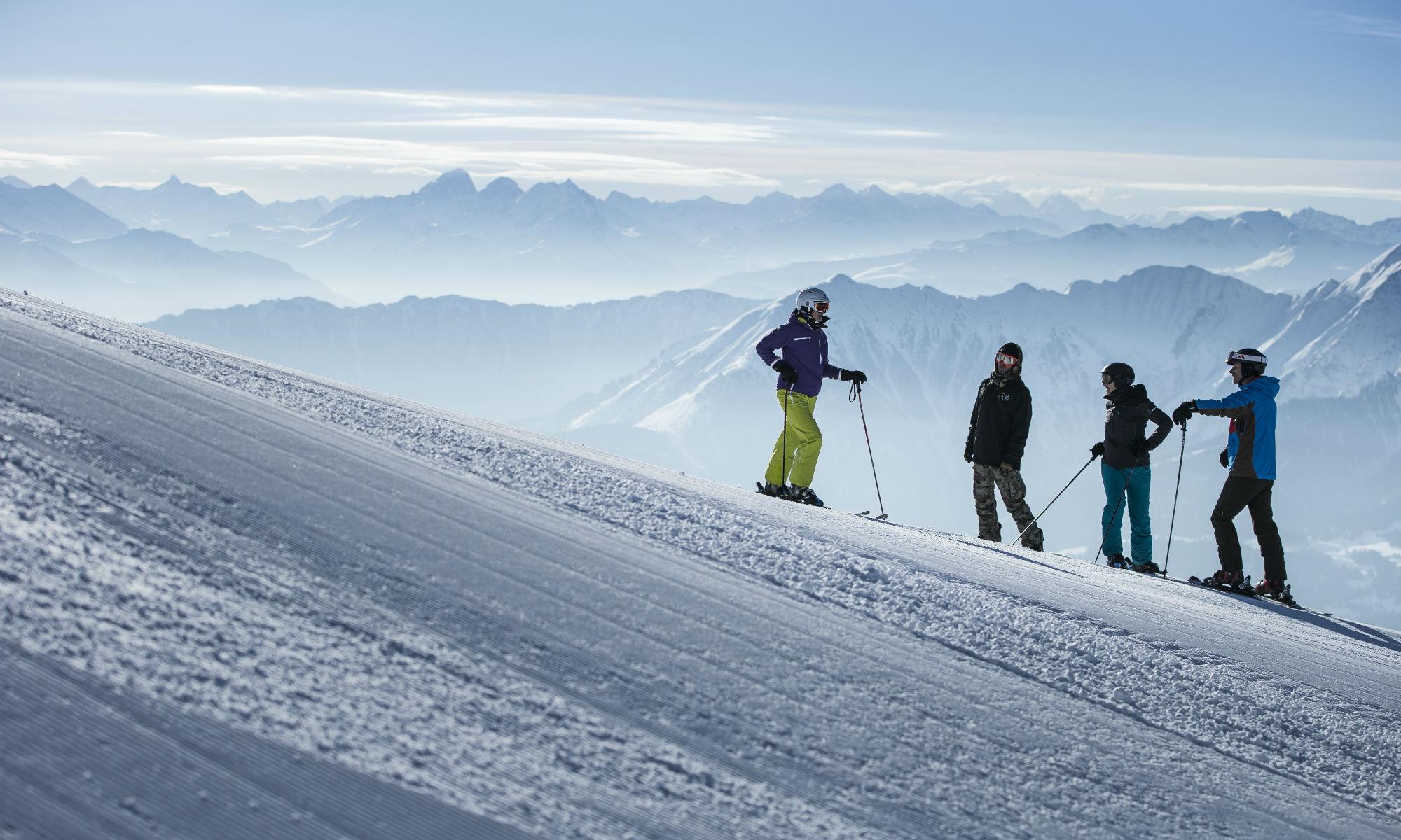 Skifahrer und ein Snowboarder beim Skikurs auf einer Piste im Skigebiet Laax-Flims-Falera.