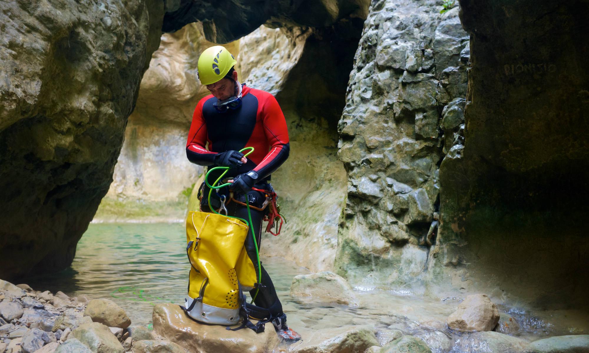 Dans un canyon, un canyoniste sort une corde de son sac à dos.
