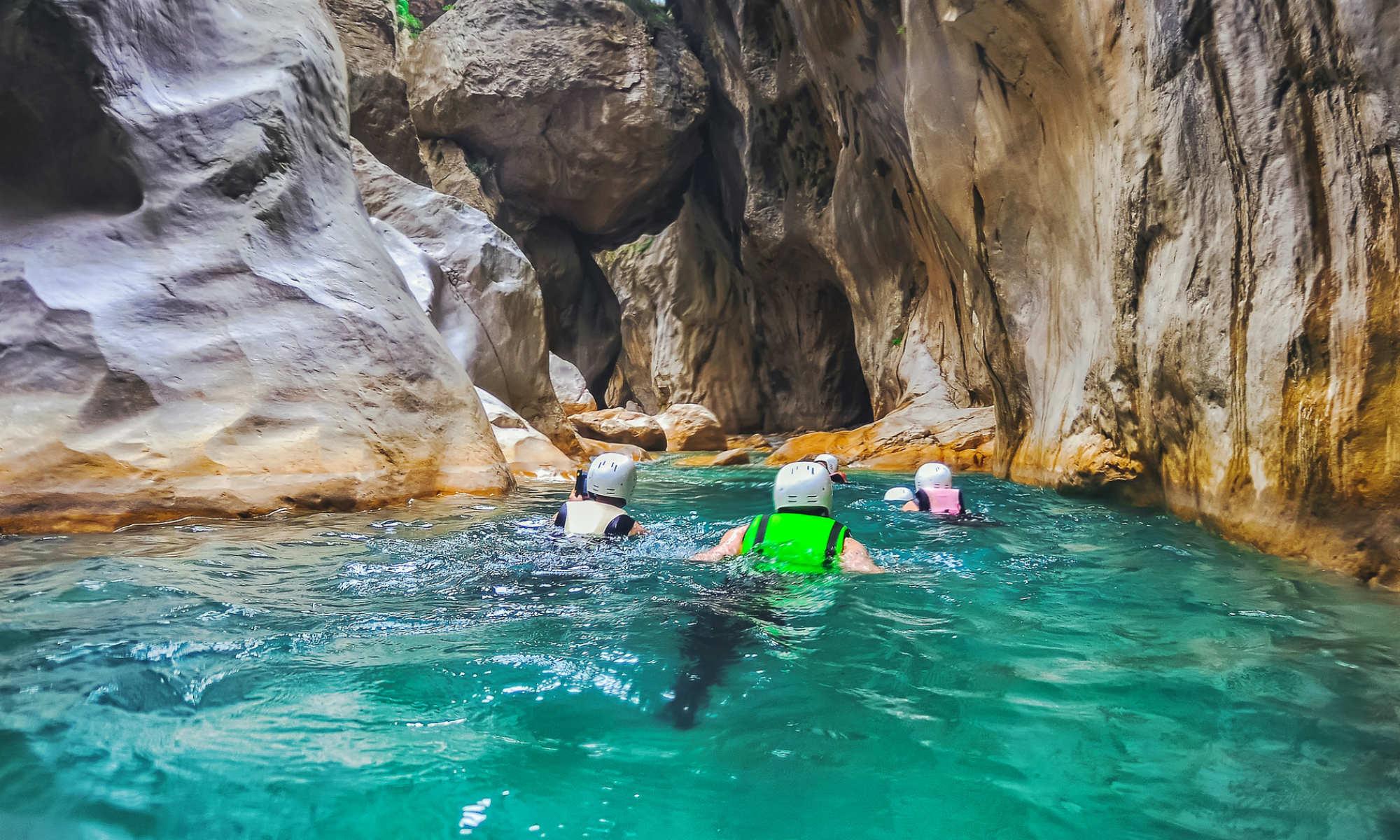 3 personnes nagent dans l'eau turquoise d'un canyon.