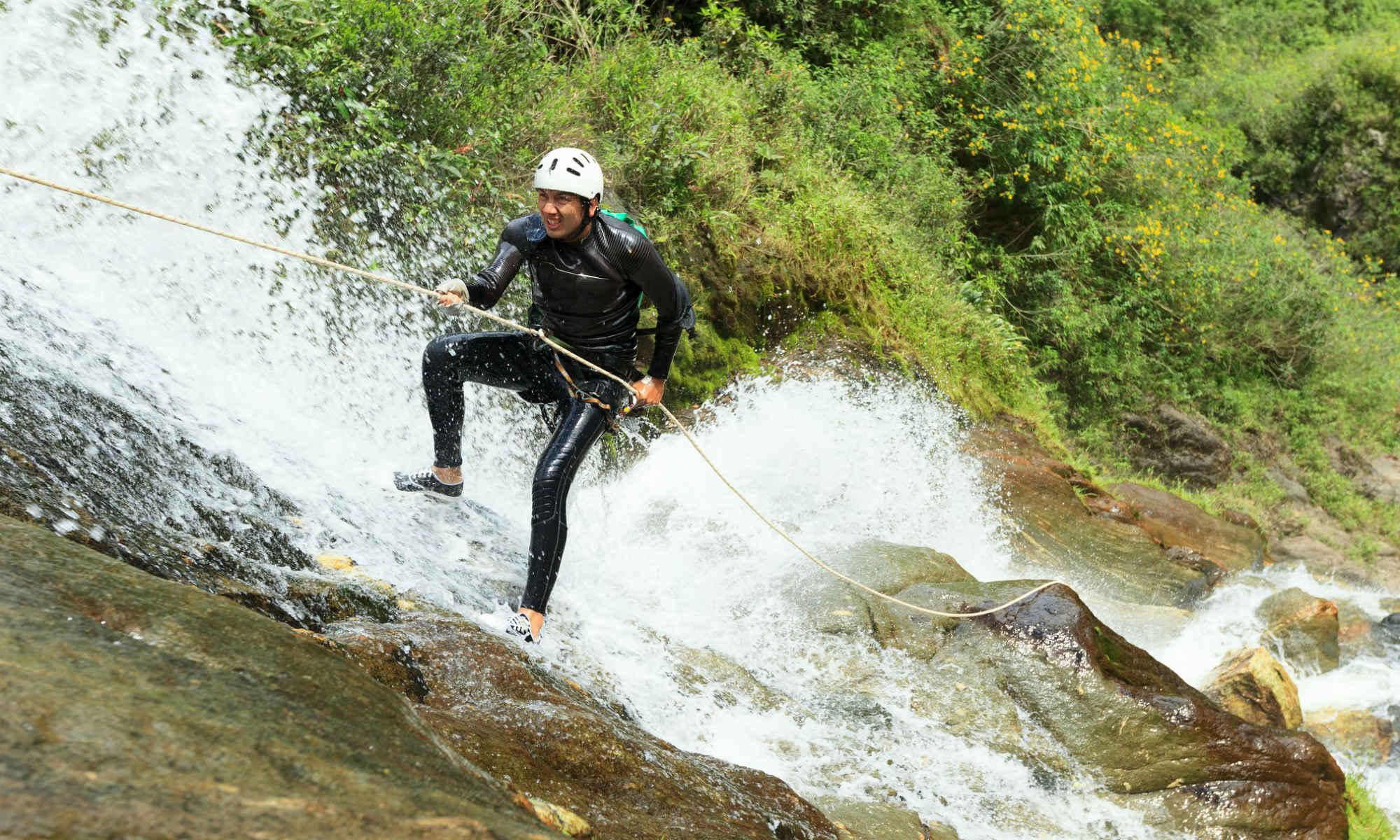 Un canyoniste descend une cascade en rappel.