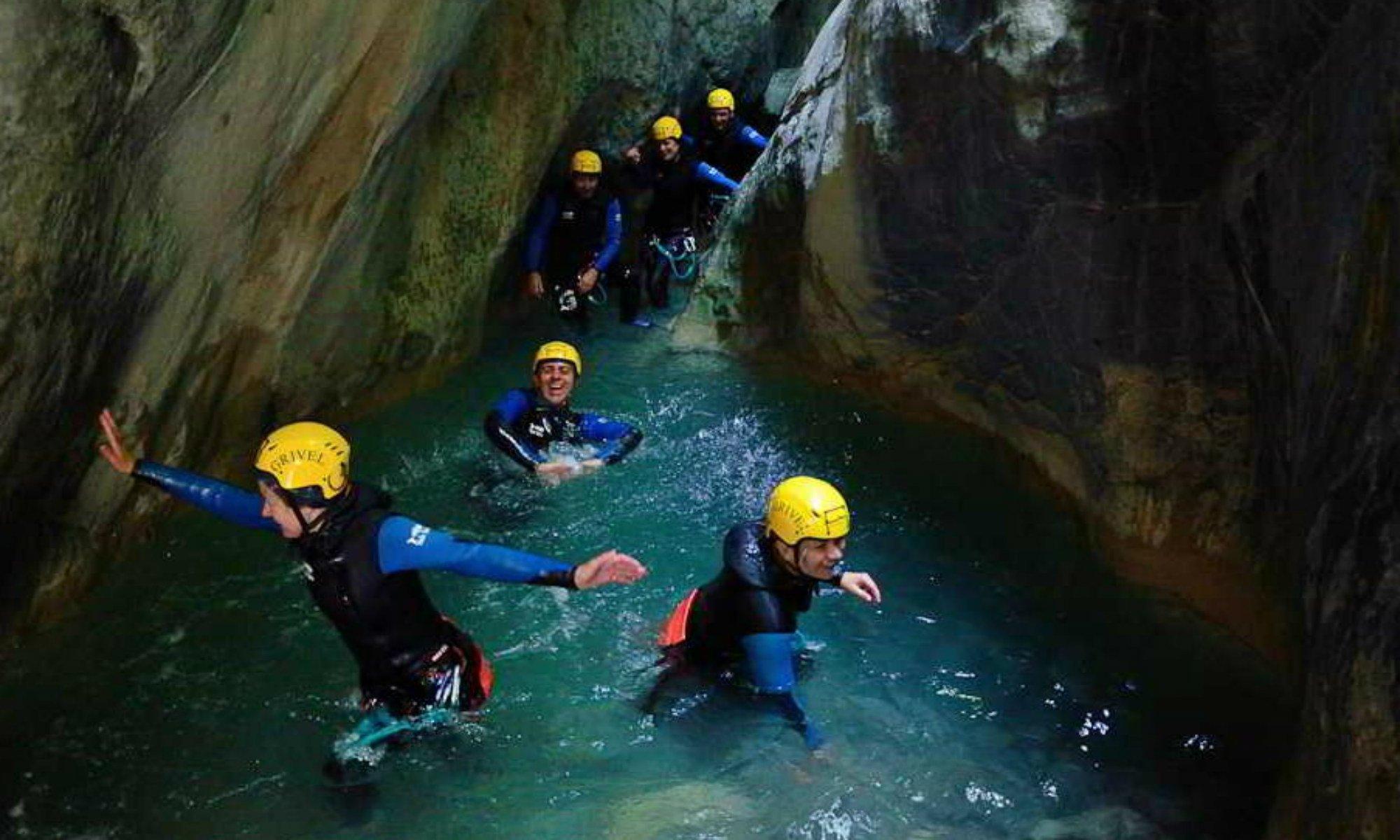 Des canyonistes se faufilent dans l'eau entre les deux parois d'un canyon.