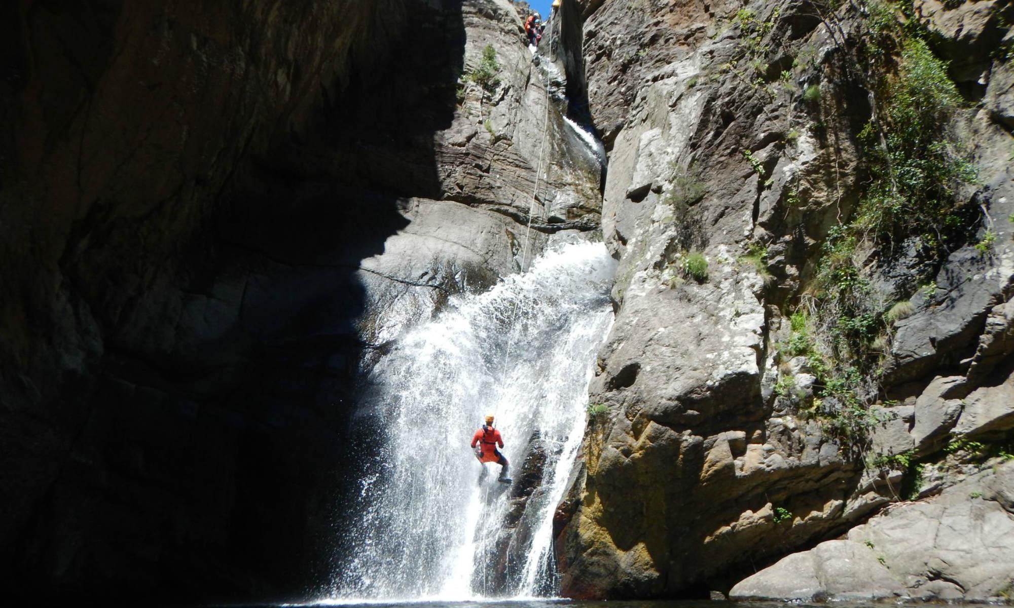 Un canyoniste descend en rappel le long d'une cascade.