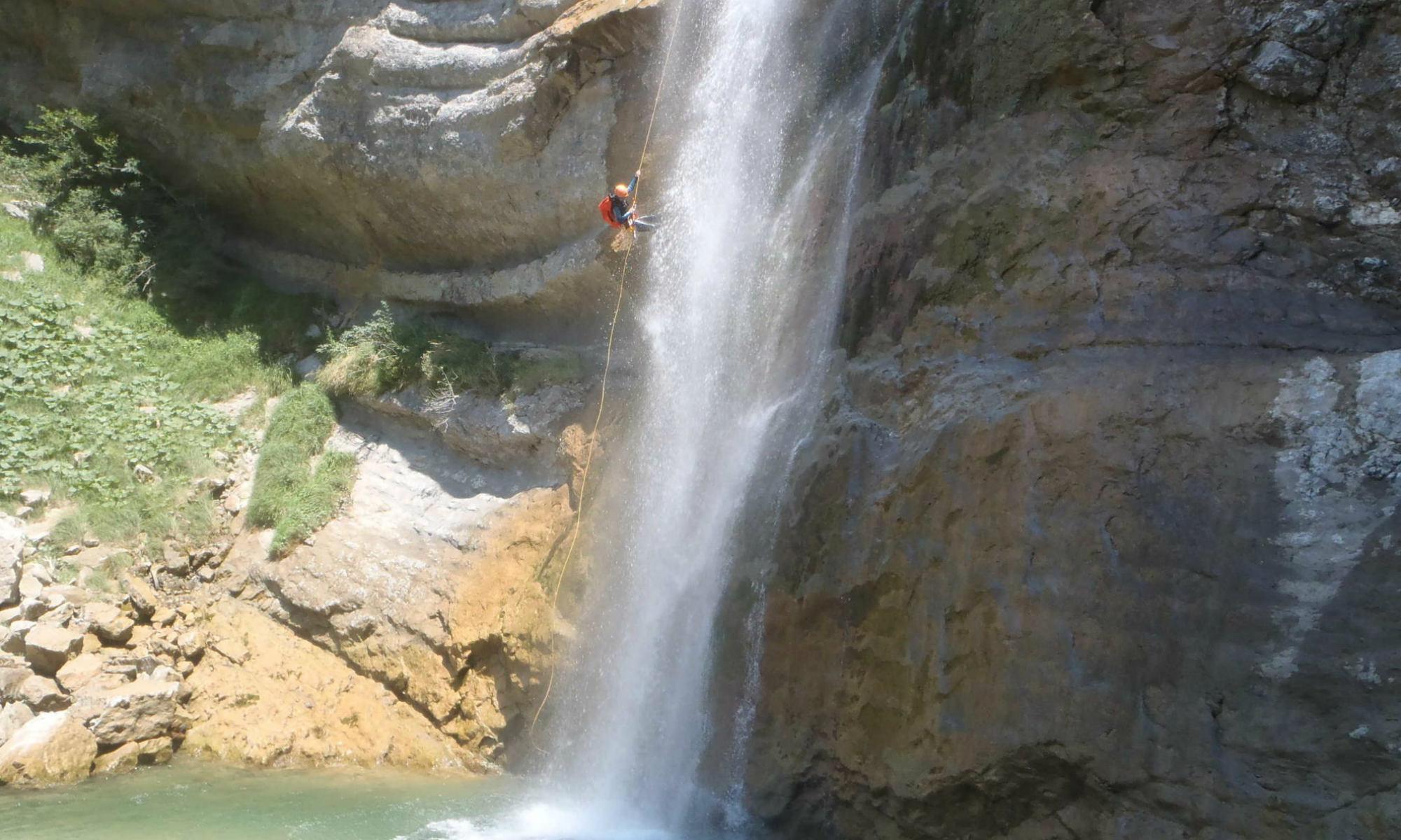 Un canyoniste descend une cascade en rappel dans le Vercors.