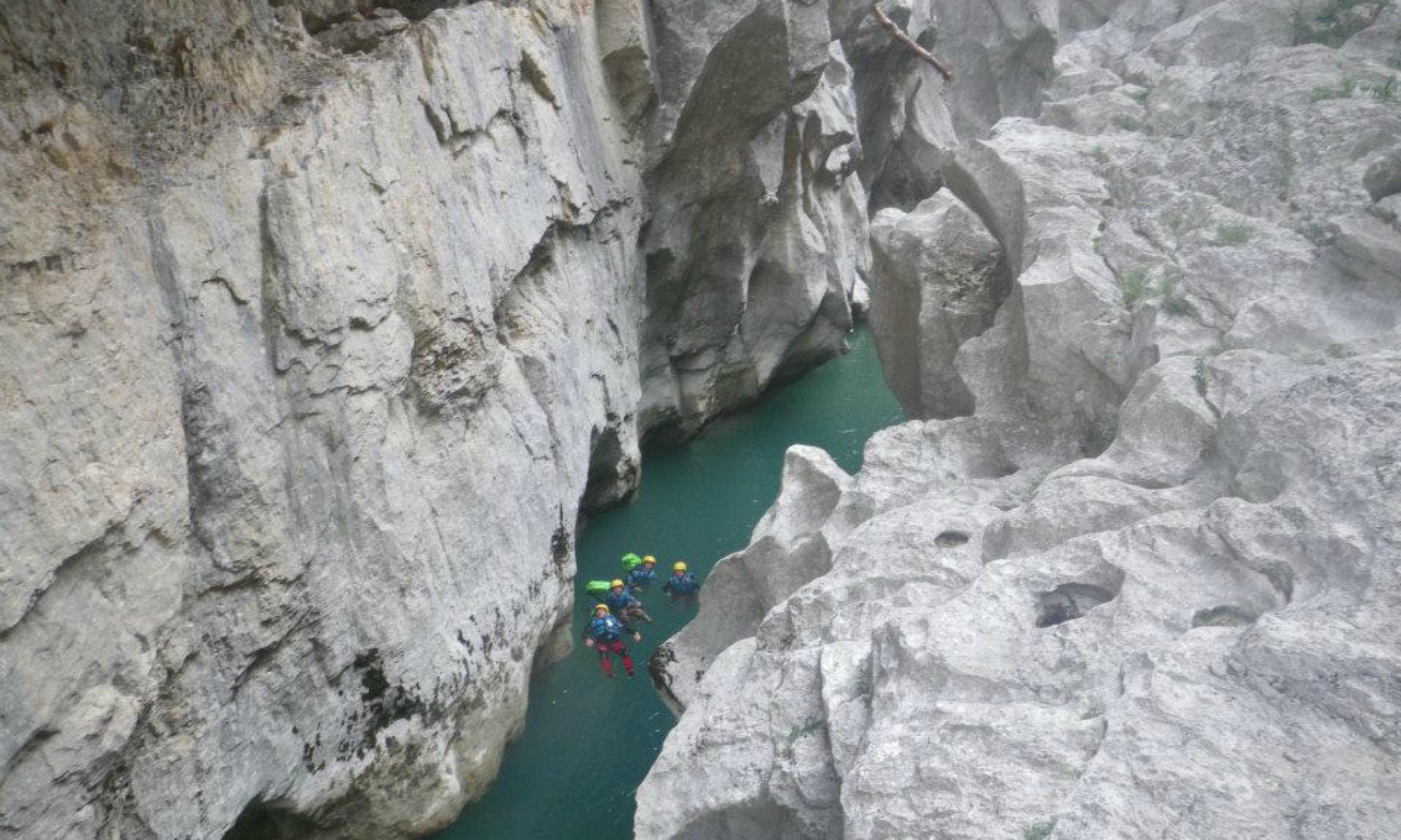 Des canyonistes dans l'eau turquoise du Verdon entre deux hautes falaises blanches.