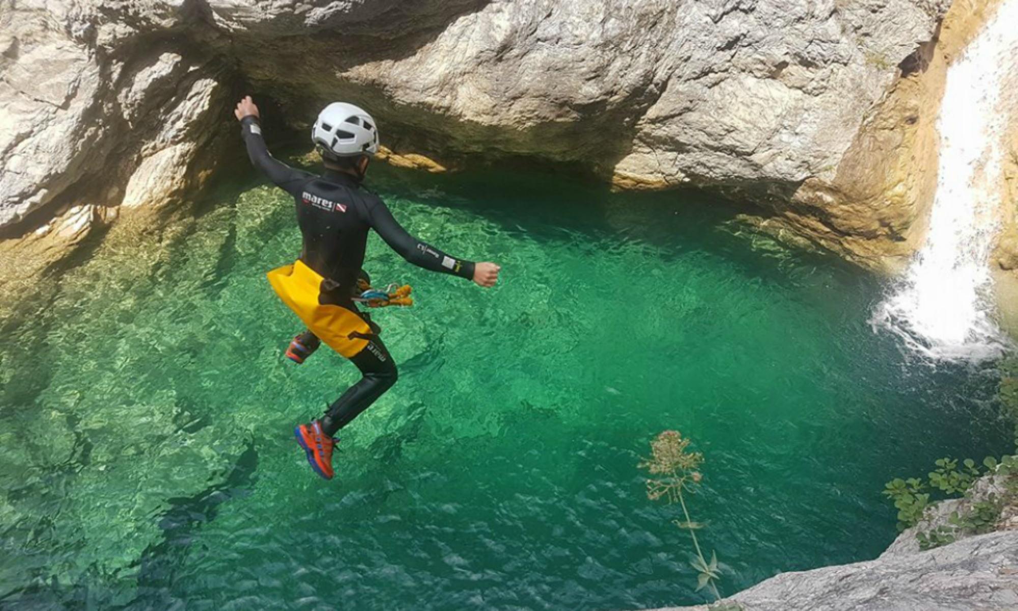 Saut dans une vasque d'eau turquoise transparente lors d'un parcours de canyoning en Italie.