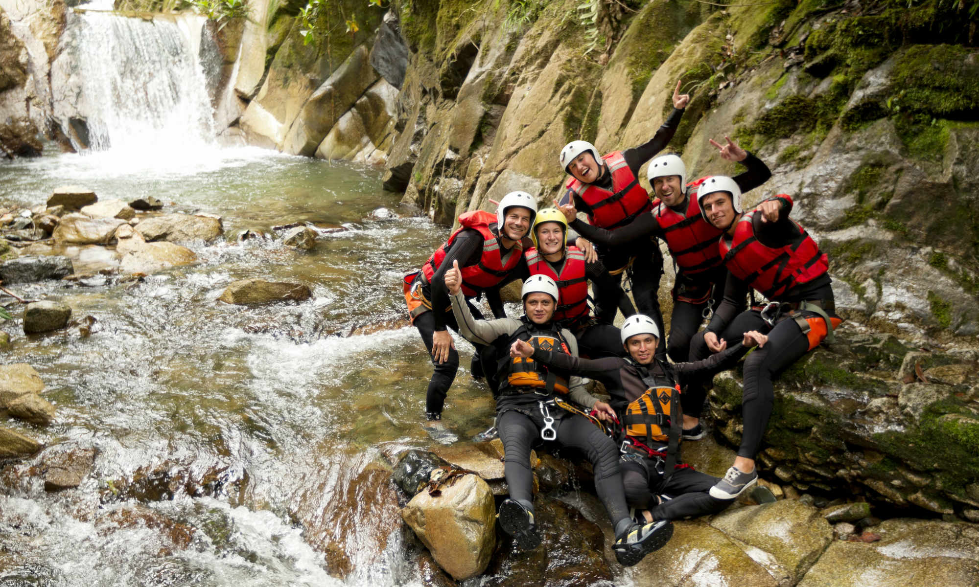Dans un canyon, un groupe d'amis prend la pose devant une cascade.