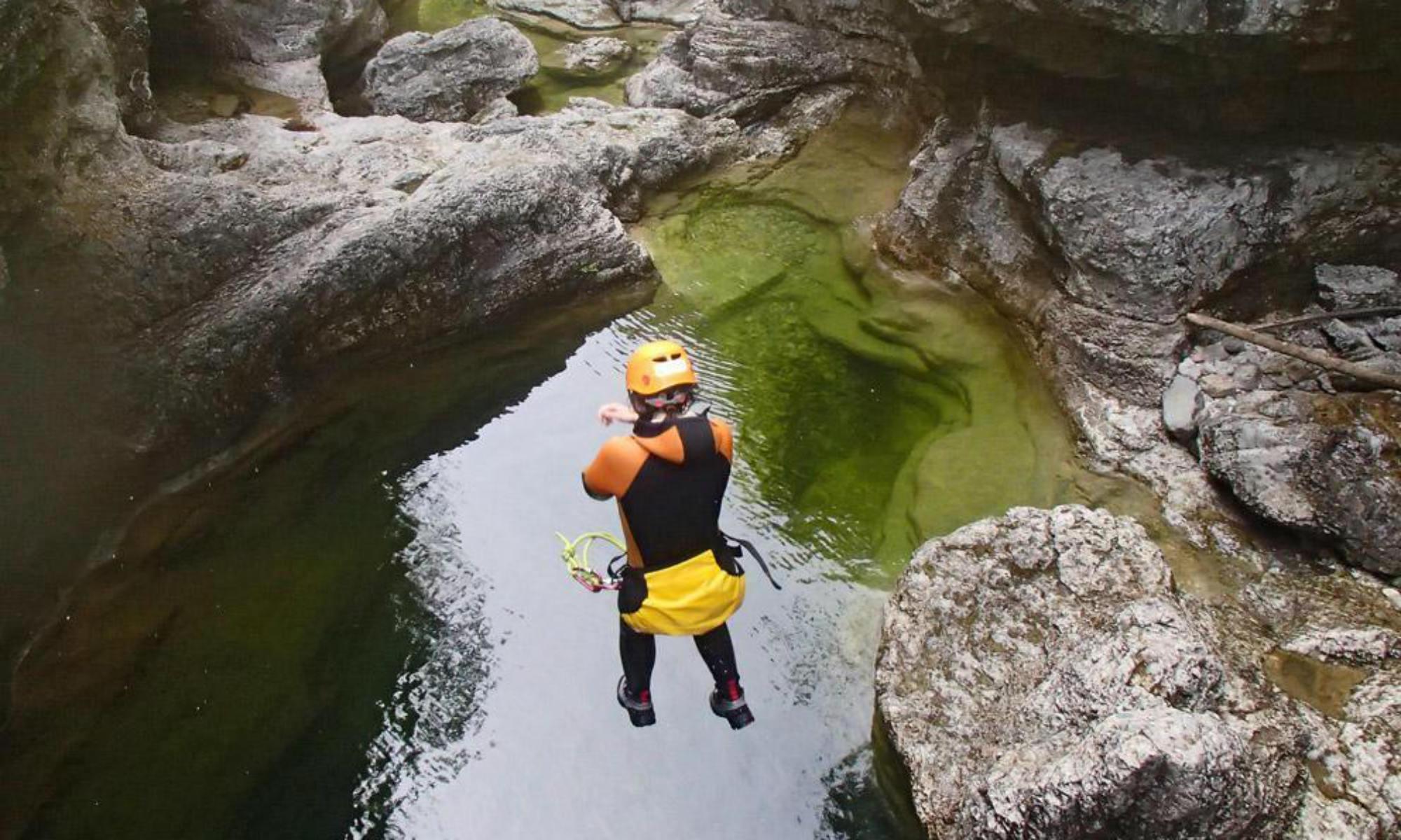 Ein Canyoning Teilnehmer springt bei einer Tour in der Almbachklamm in einen smaragdgrünen Wassertümpel.
