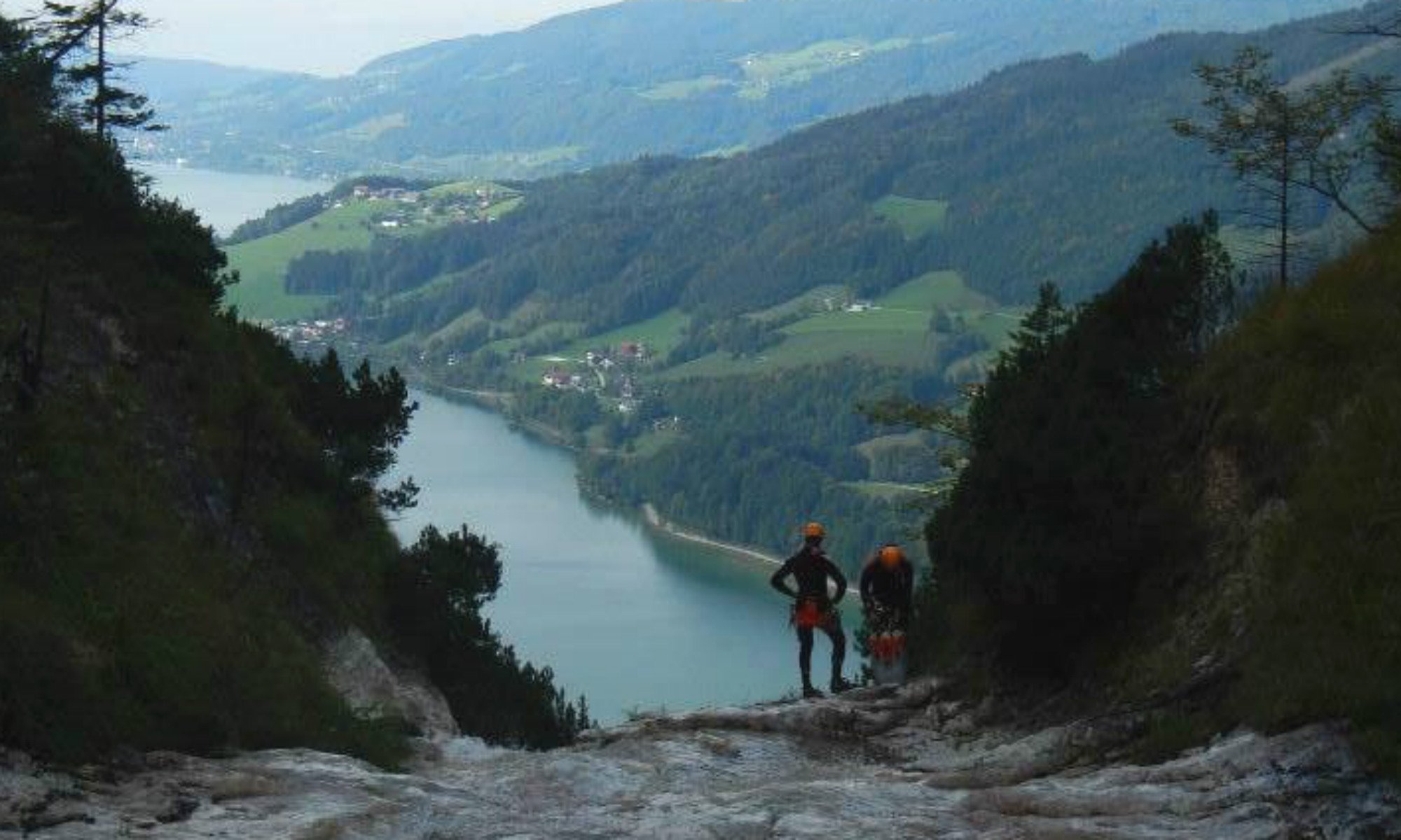 2 Teilnehmer einer Canyoning Tour in Salzburg stehen auf einem Felsen und blicken auf den Mondsee.