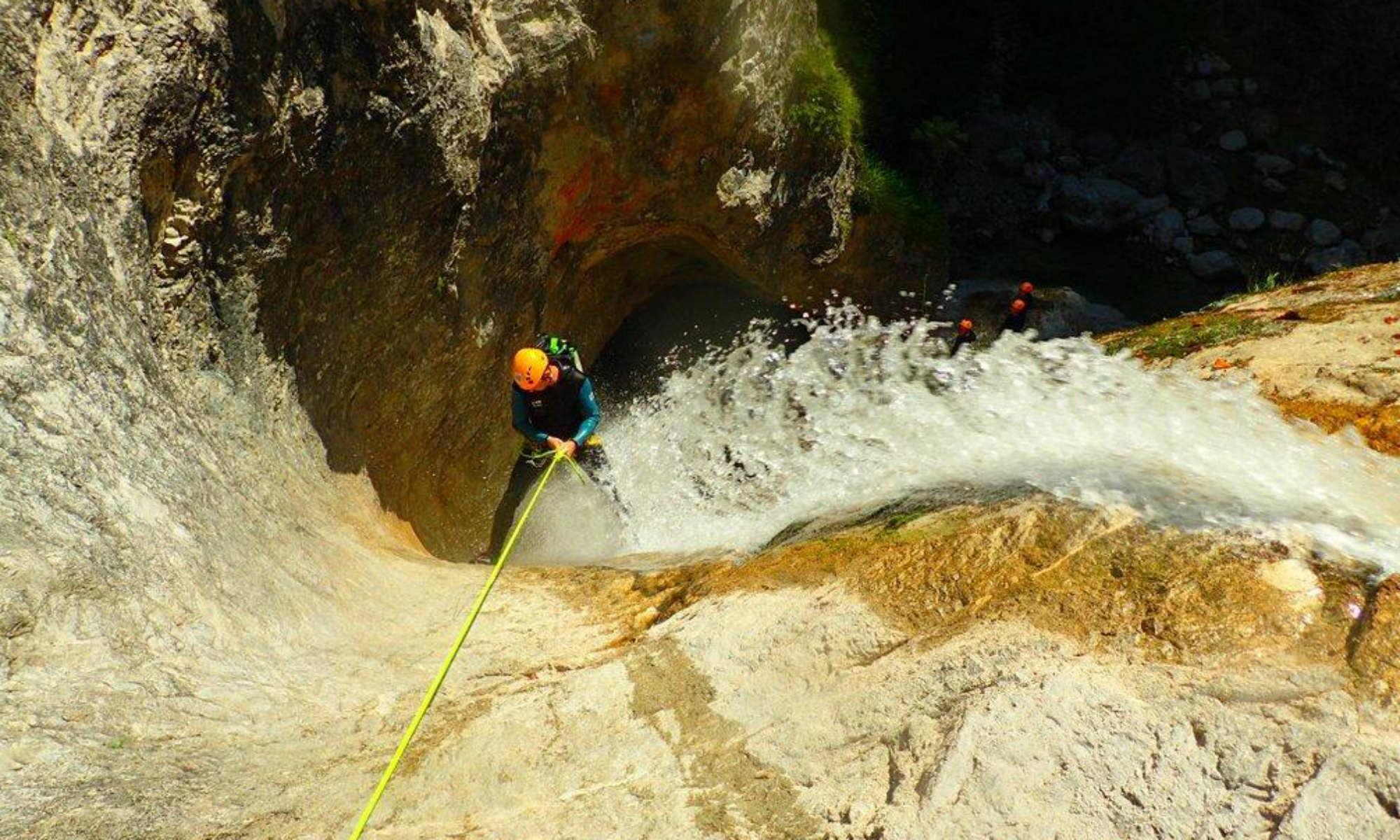 Ein Schluchtenwanderer seilt sich beim Canyoning in Salzburg an einem Wasserfall ab.