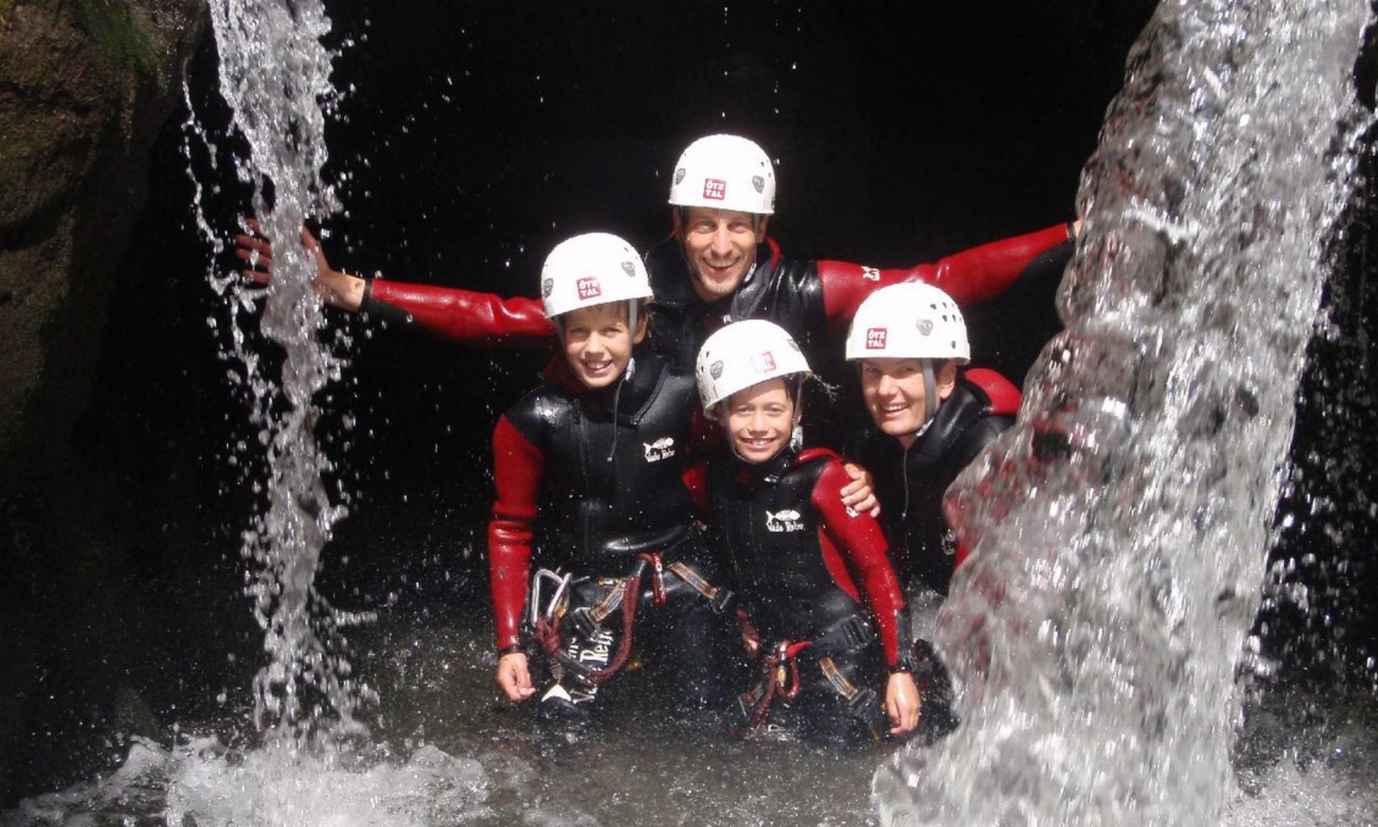 Eine Familie beim Canyoning in Tirol in einem Tümpel neben einem Wasserfall.