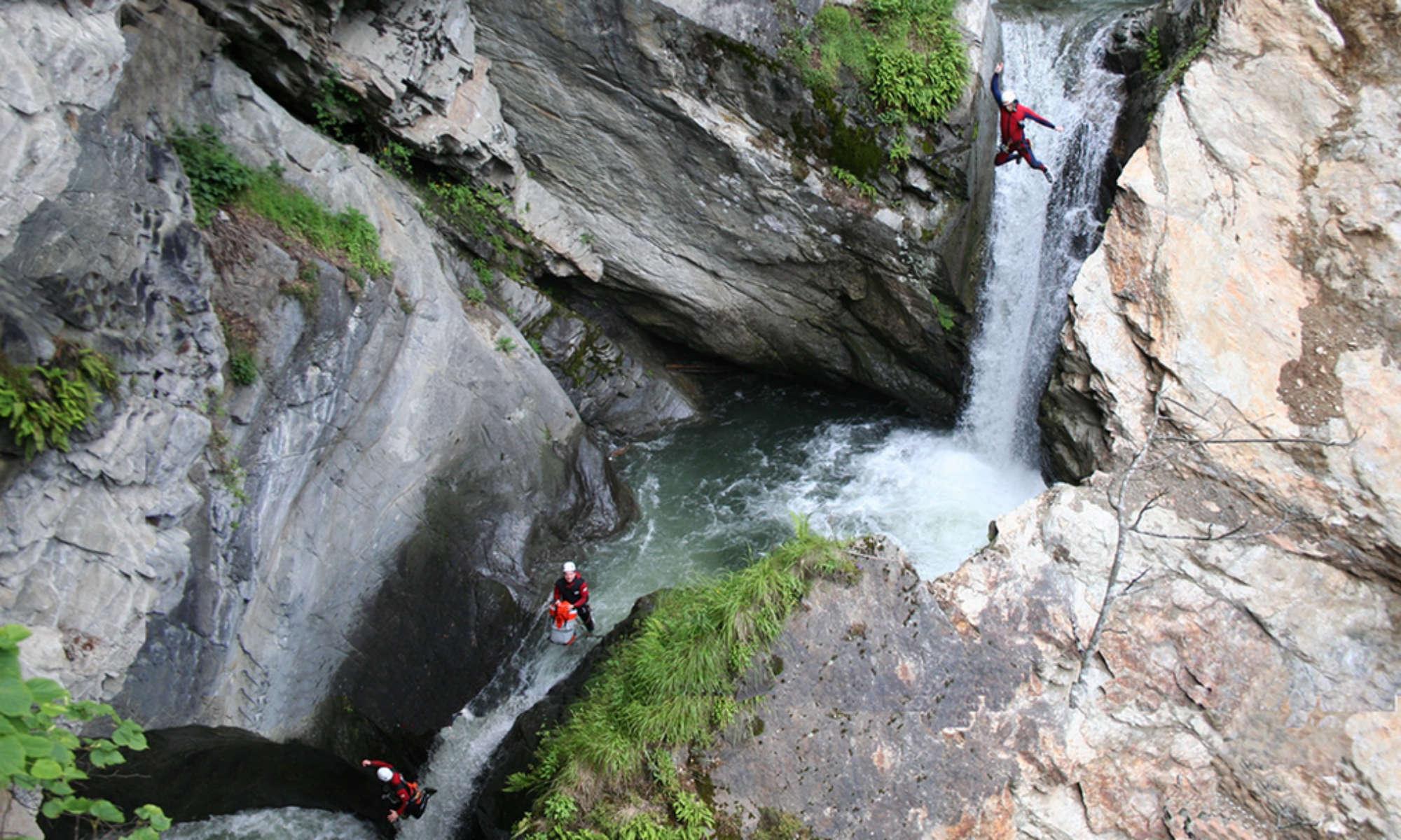 Eine Gruppe springt beim Canyoning in Tirol einen Wasserfall der Auerklamm hinunter.
