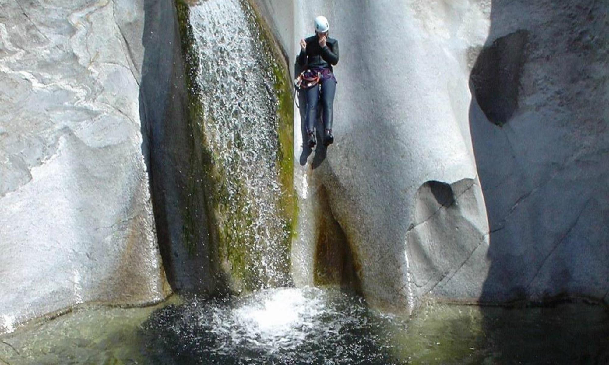 Ein Teilnehmer einer Schluchtenwanderung rutscht beim Canyoning in Tirol eine Wasserrutsche hinab.