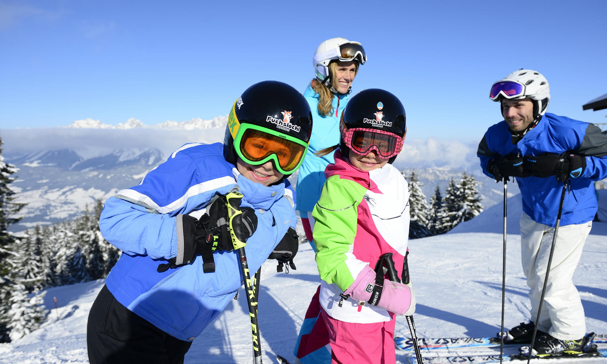 Een familie skiet in de Alpen.