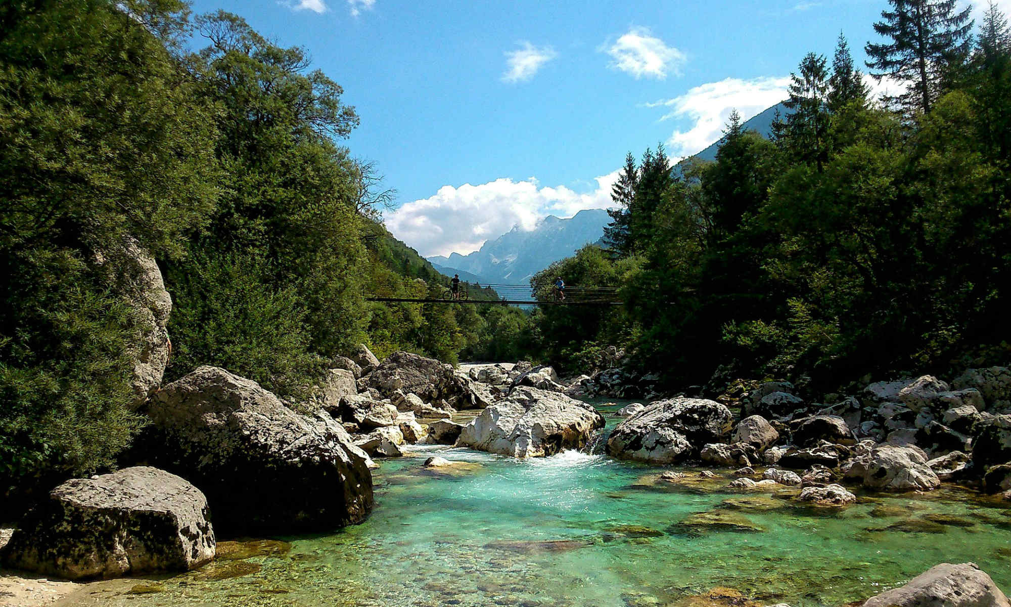 Il panorama molto verde della Slovenia si alterna nella foto con i massi e il fiume Isonzo.