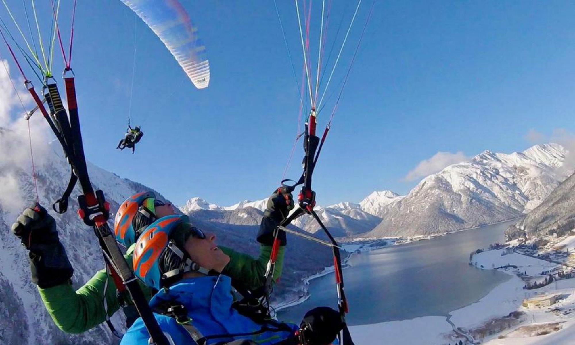 Zwei Paraglider über der Winterlandschaft des Achensees.