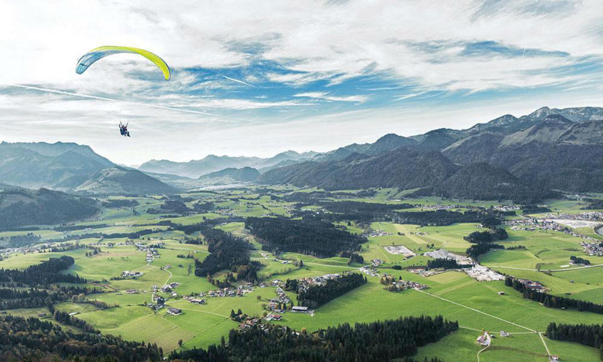 Ein Paragleiter über der grünen Landschaft des Kaiserwinkls.