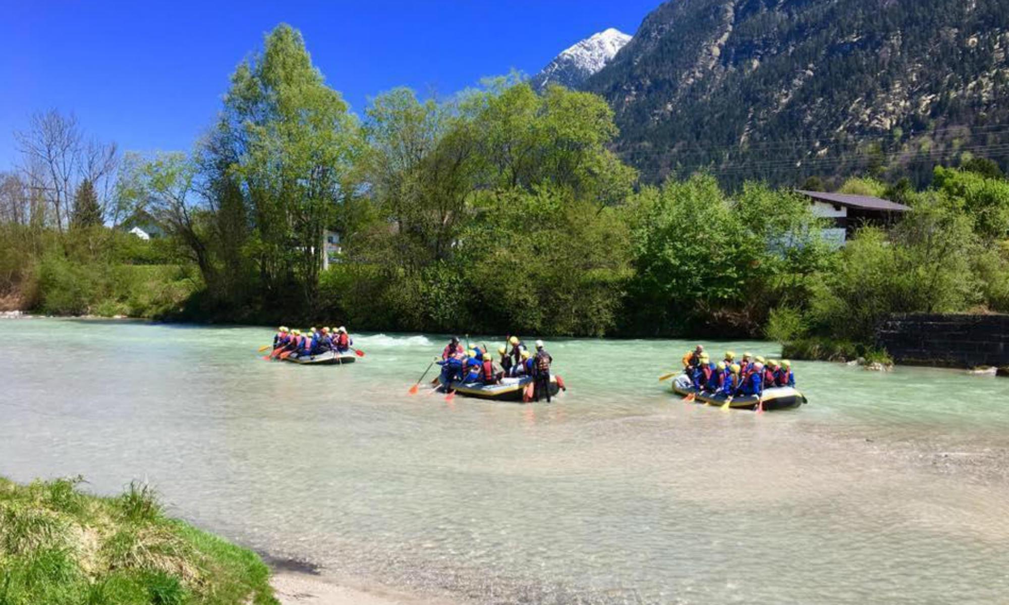 Drei Gruppen in Schlauchbooten beim Rafting in Bayern.