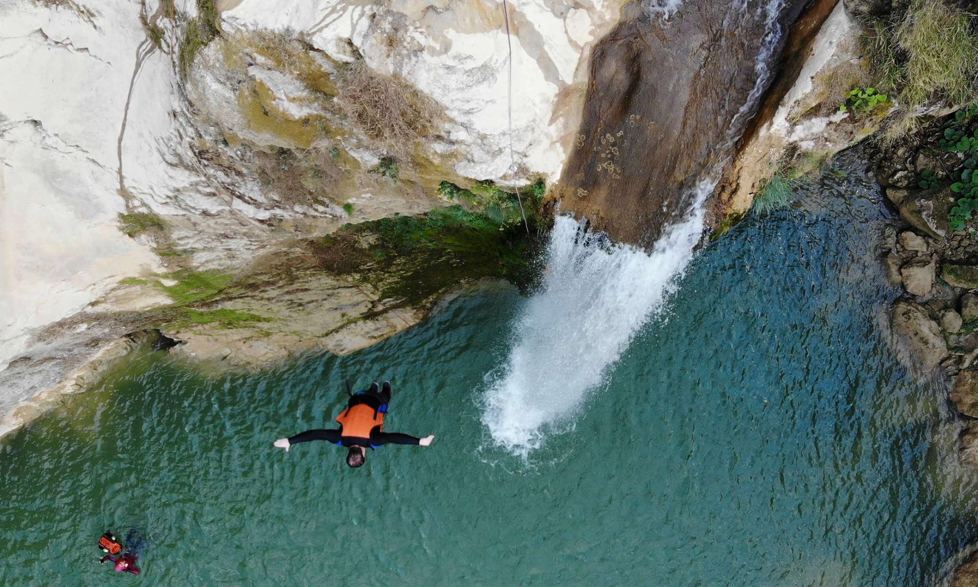 Un canyoniste saute dans l'eau turquoise d'une rivière.
