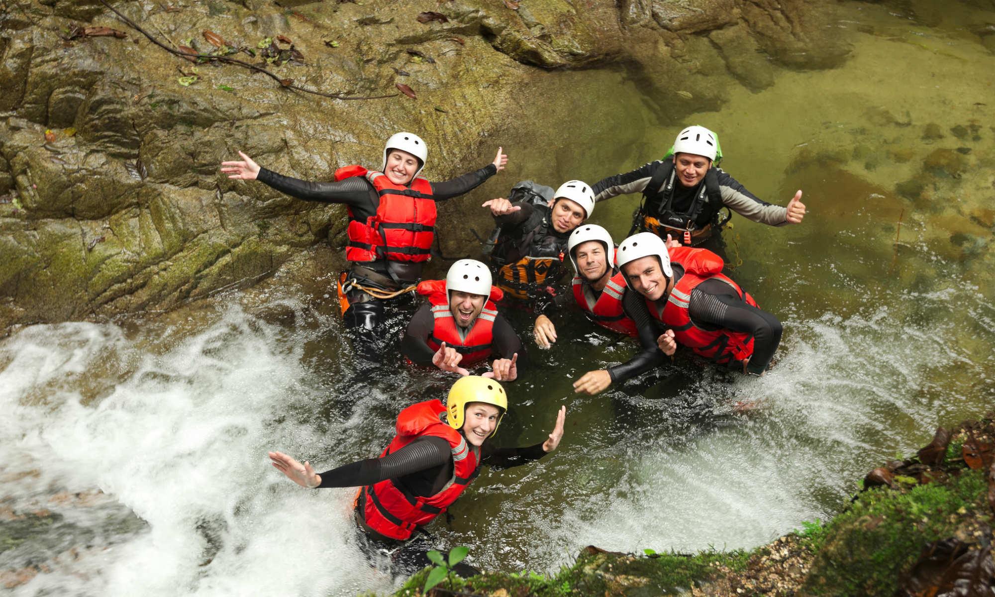 Un groupe d'amis tout sourire dans l'eau tumultueuse d'un canyon.