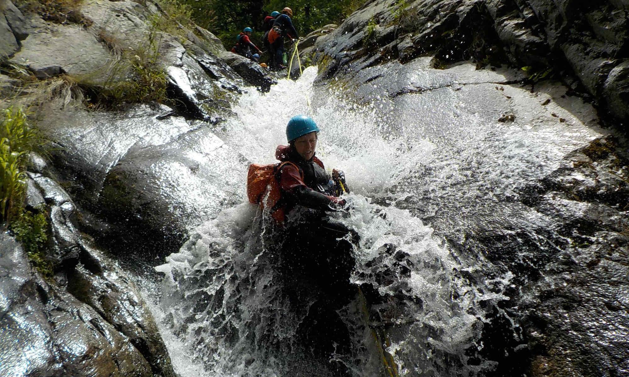 Une jeune femme descend une cascade en rappel dans les Pyrénées.